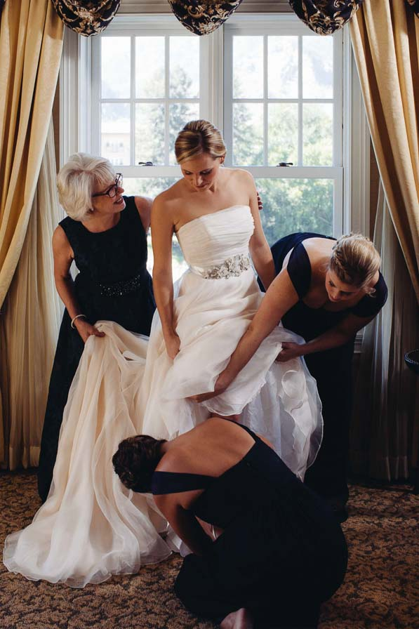 Bride is helped getting into wedding dress.