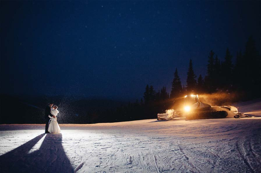 Couple kiss on ski slope at night with grooming machine behind them.