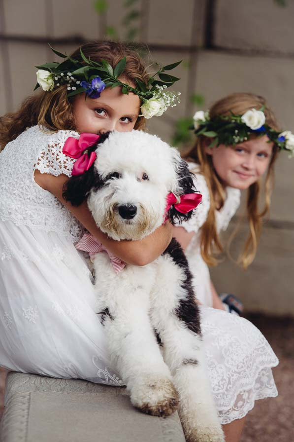Flower girl hugs dog dressed up in pink ribbons.