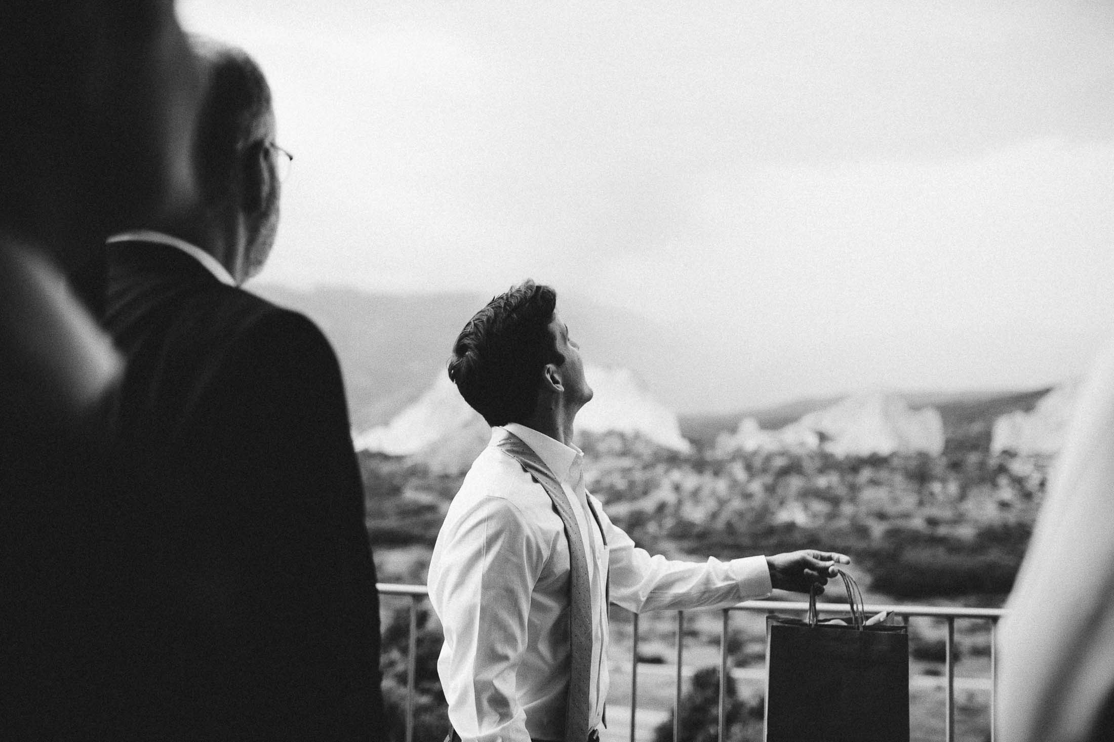 Black and white picture of groom looking up at the sky.