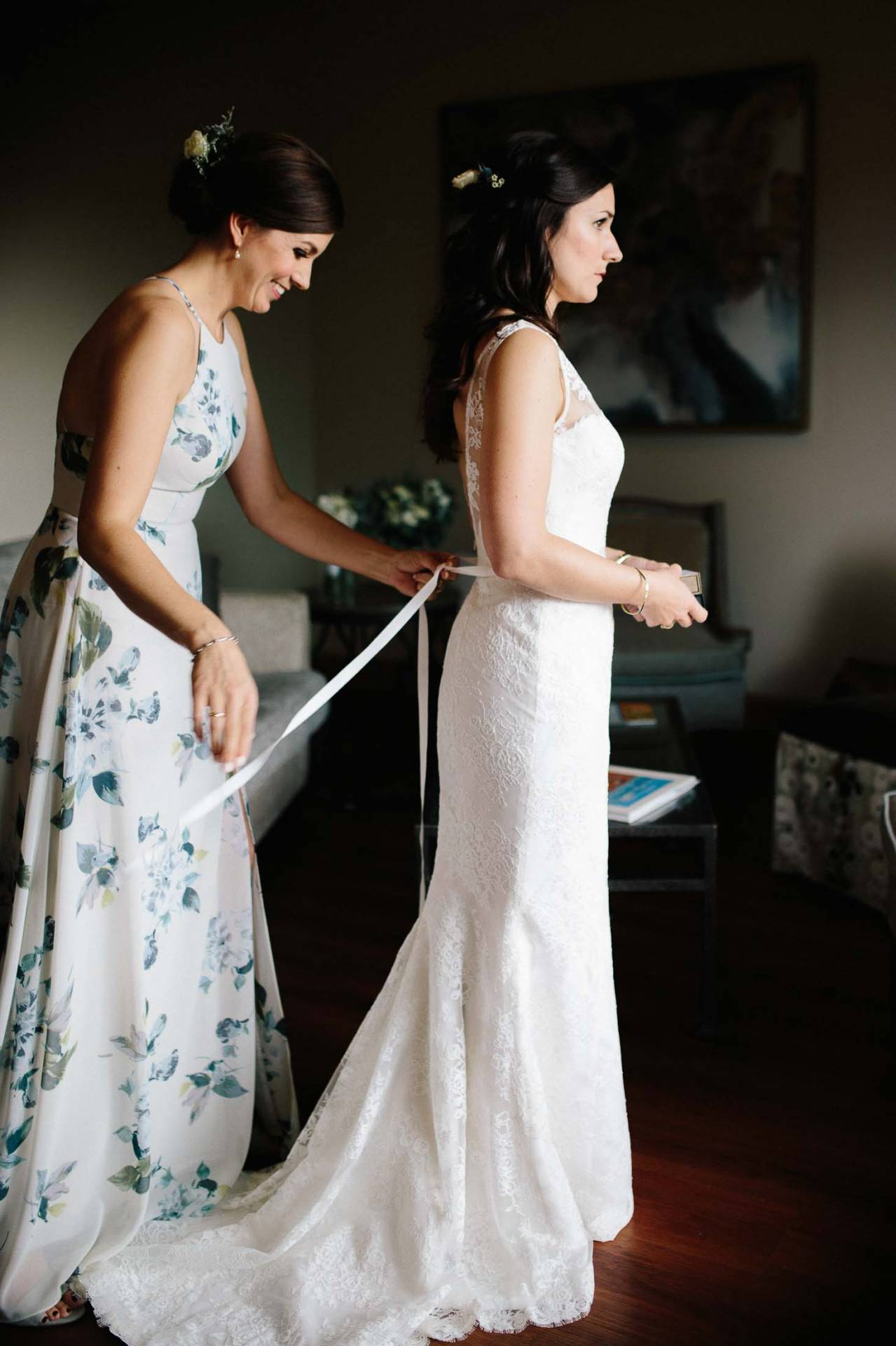 Bride getting dressed with help with sister.