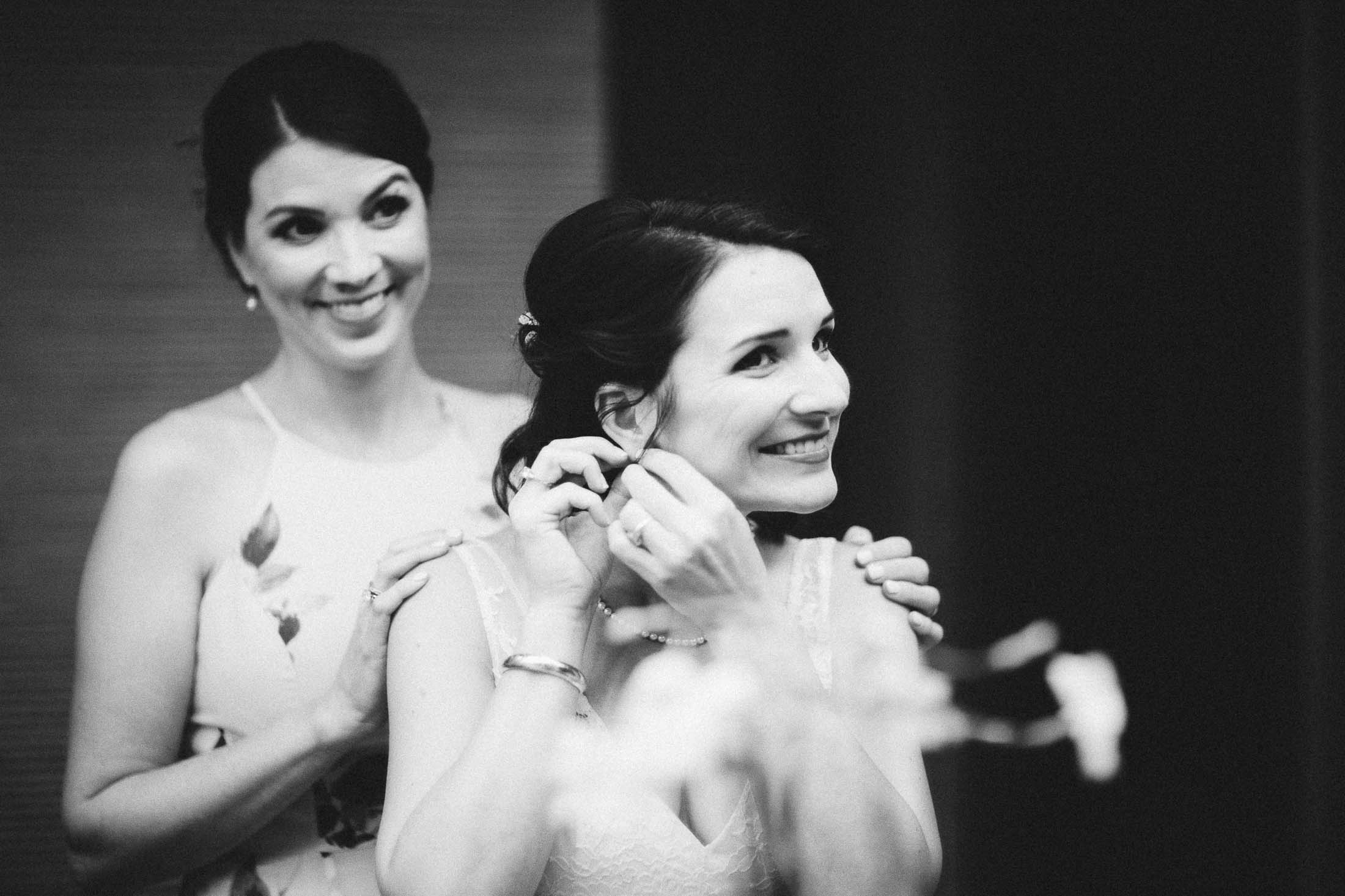 Black and white picture of bride putting on jewelry with sister looking on.