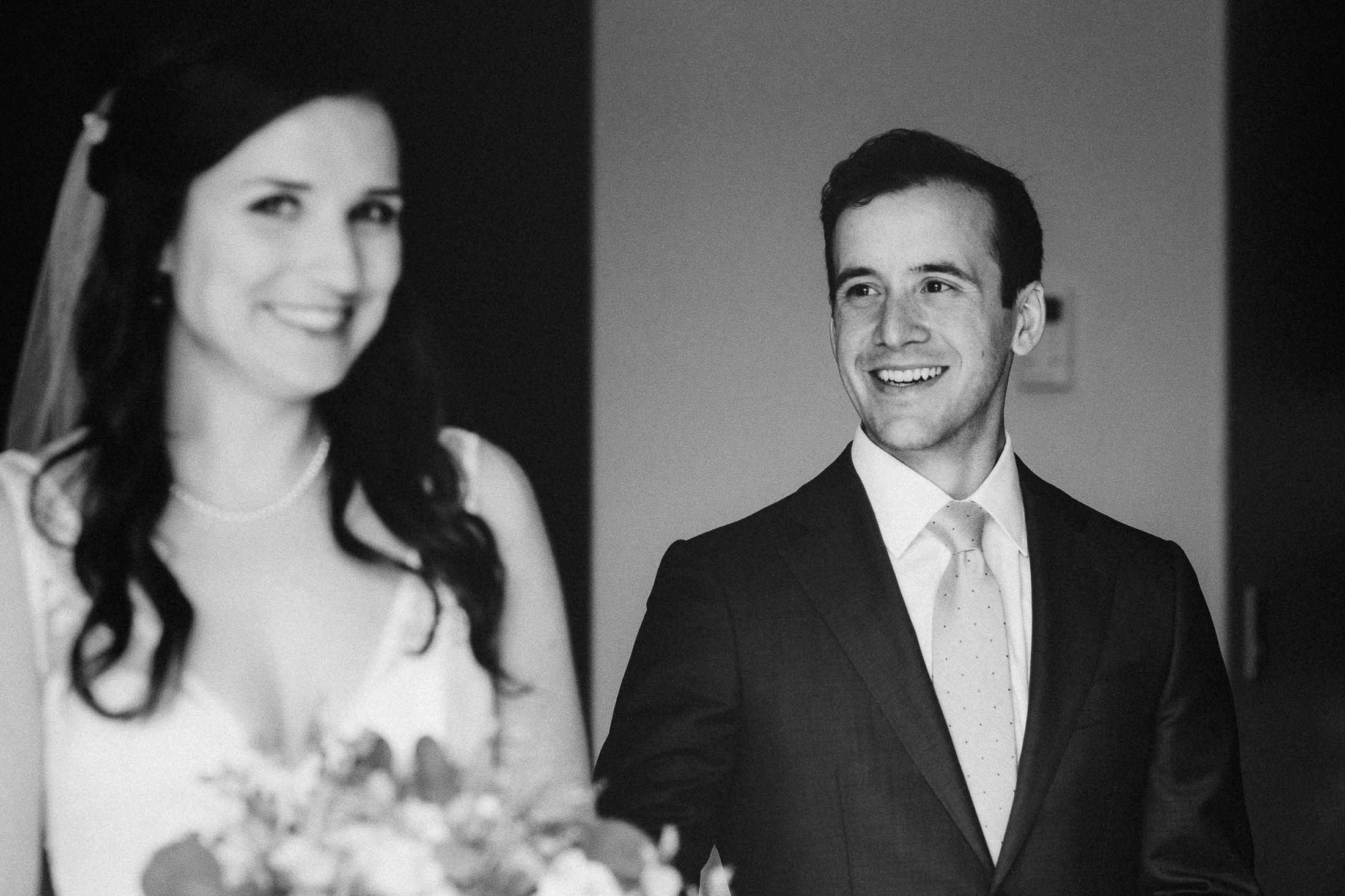 Black and white photo of groom as he sees his bride during a private moment.