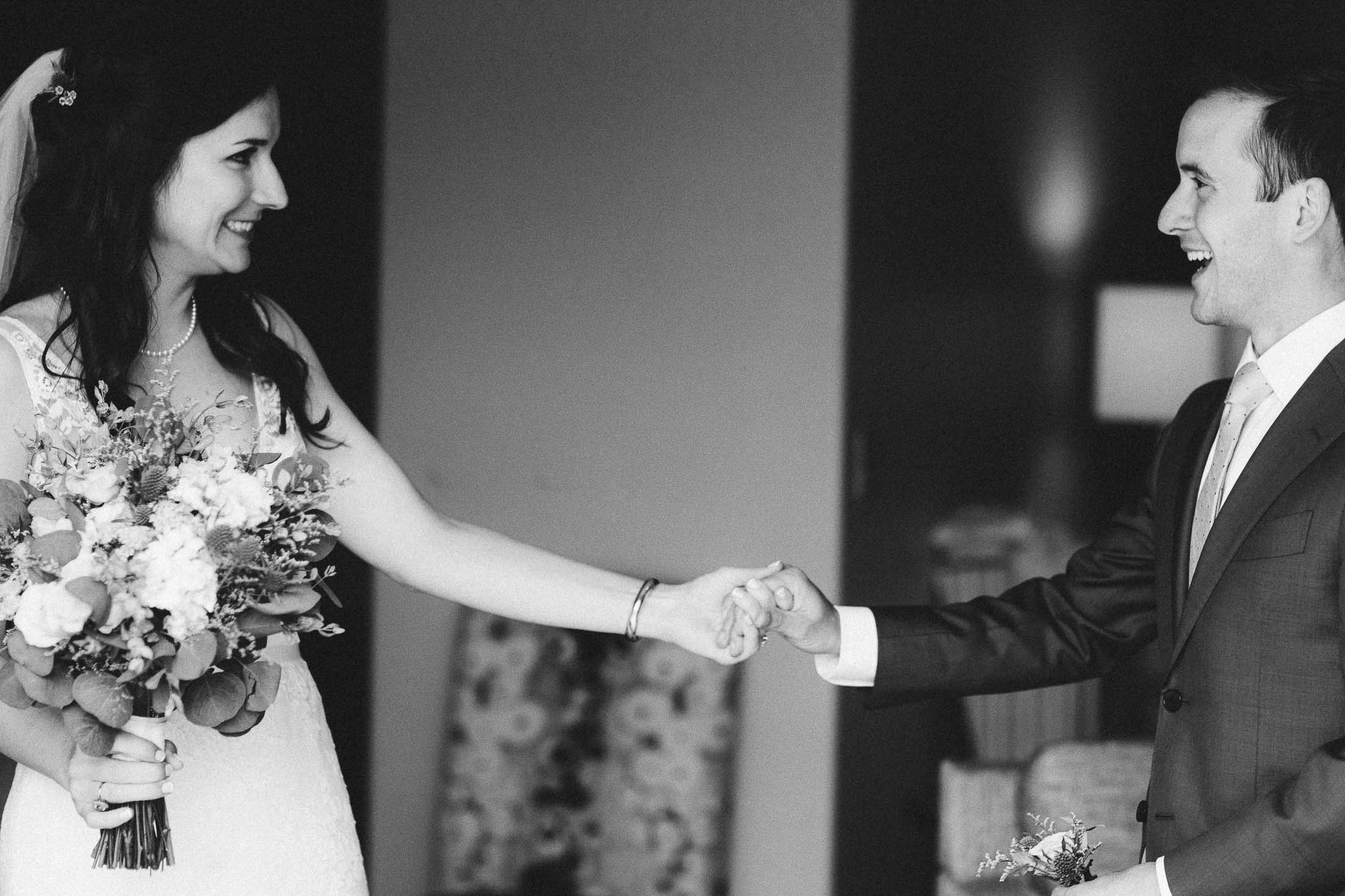 Black and white photo of bride and groom seeing each other and holding hands.
