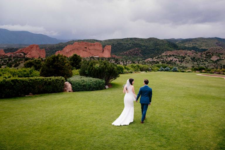 Bride and groom walk together on lawn in front of the Garden of the Gods rock formation.