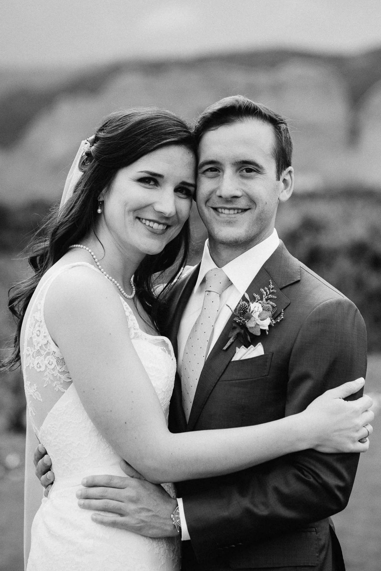 Black and white portfolio of bride and groom looking at camera.