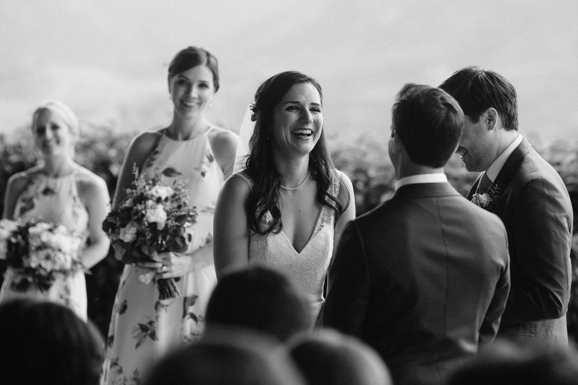 Black and white photo of bride laughing during wedding ceremony.