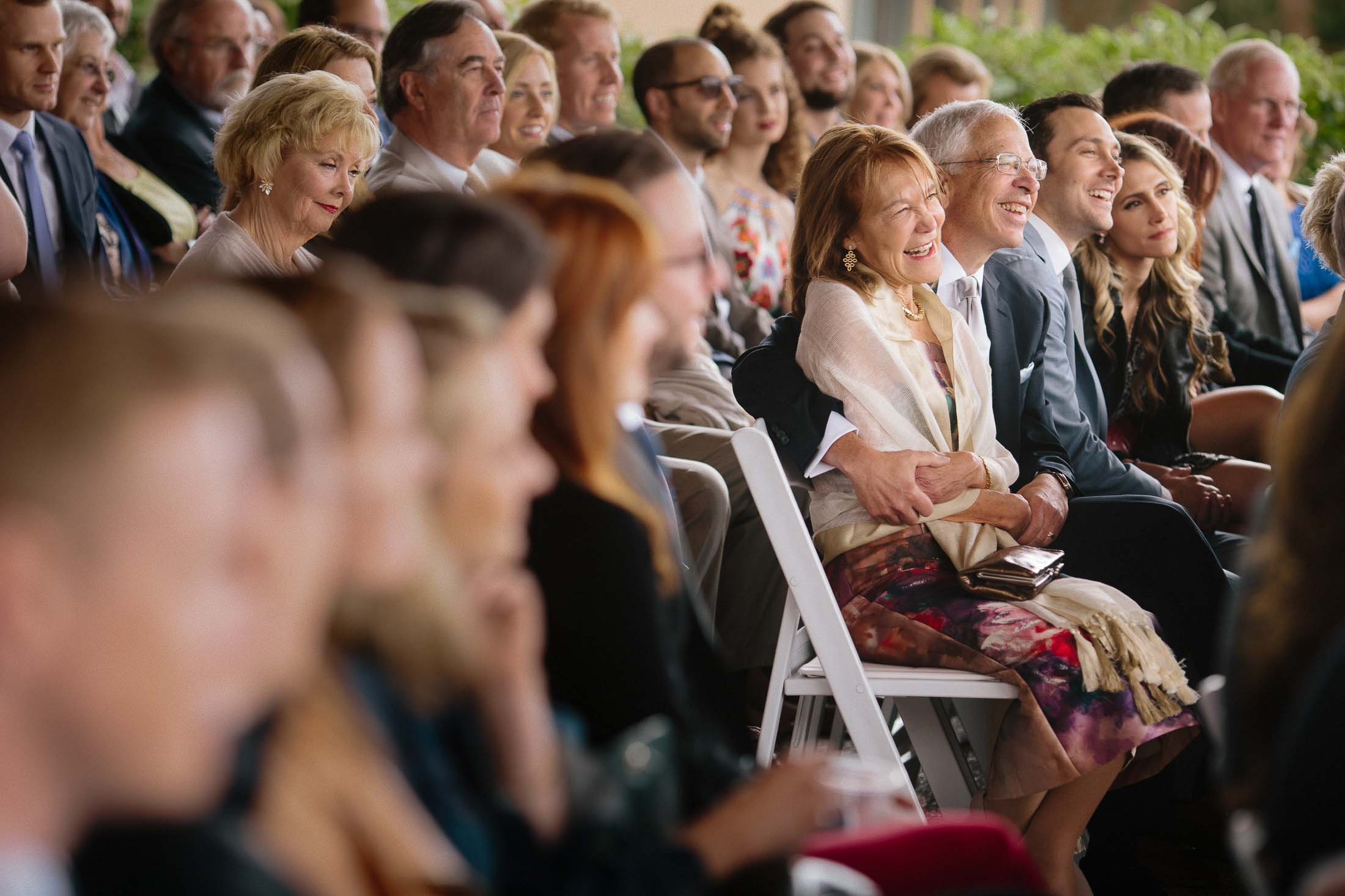 Audience laughs during wedding ceremony.
