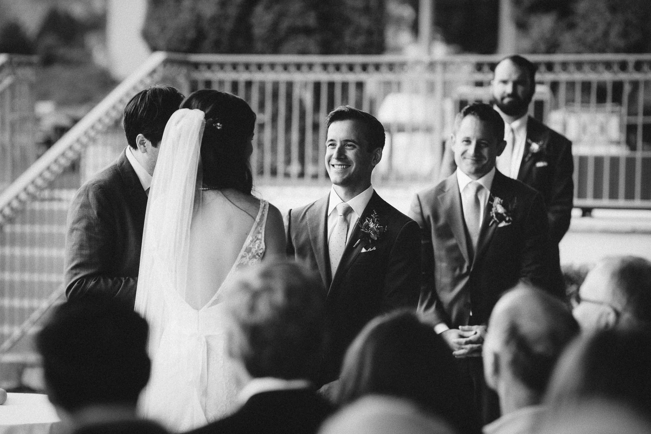 Black and white photo of bride and groom standing at the altar during ceremony.