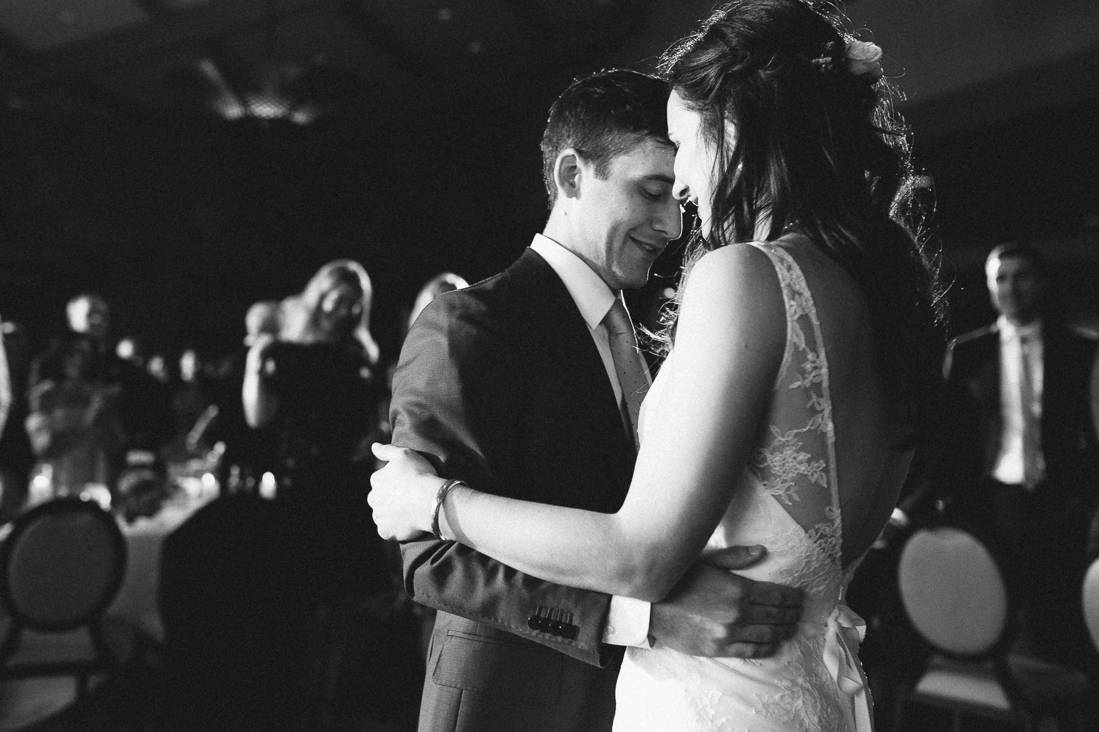 Black and white photo of bride and groom dancing together.