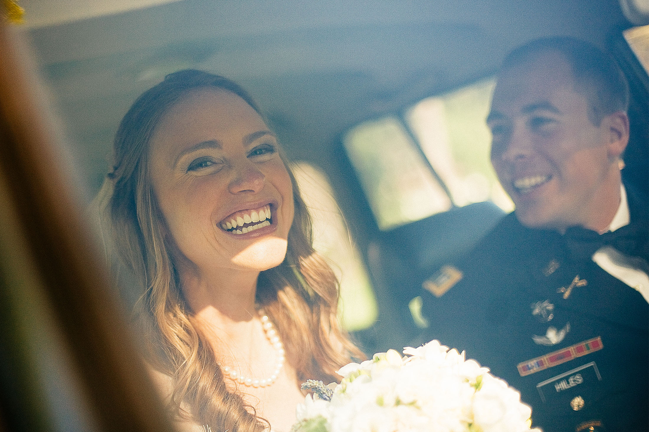 Bride with groom smile together inside a Toyota Landcruiser as they depart their wedding ceremony.