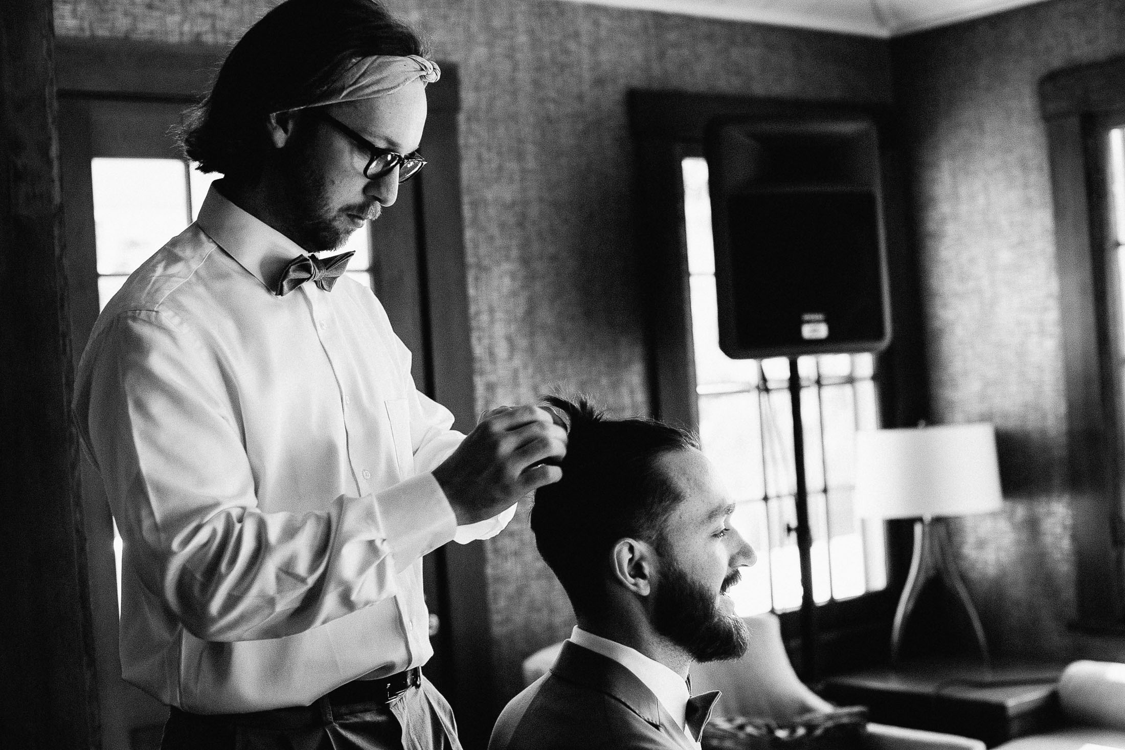 Black and white photo of groomsman fixing groom's hair inside Outlook Lodge.