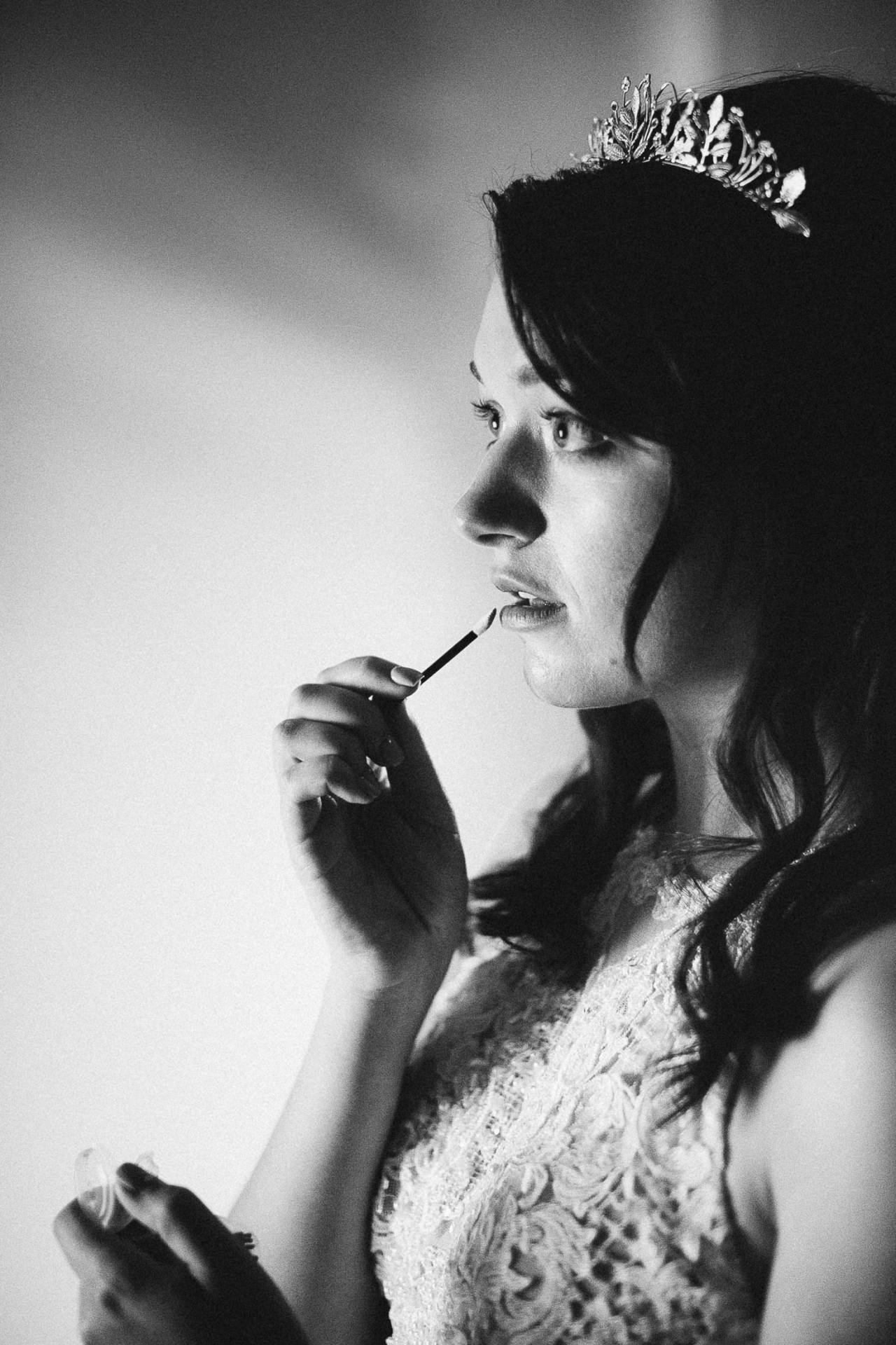 Black and white photo of bride putting on lipstick at the Outlook Lodge.