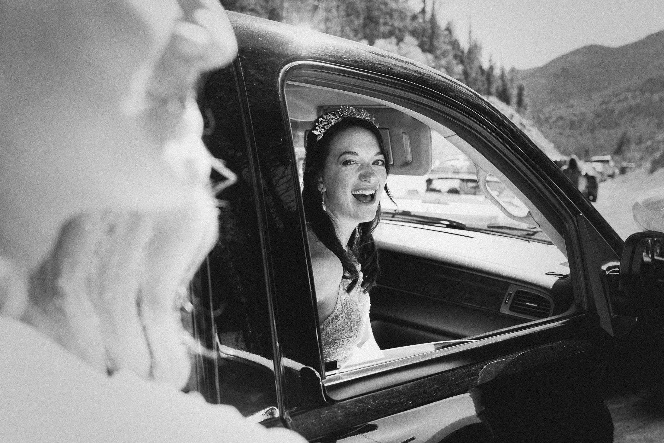 Black and white of bride laughing as she waits for the ceremony in a car outside of Bishop Castle.