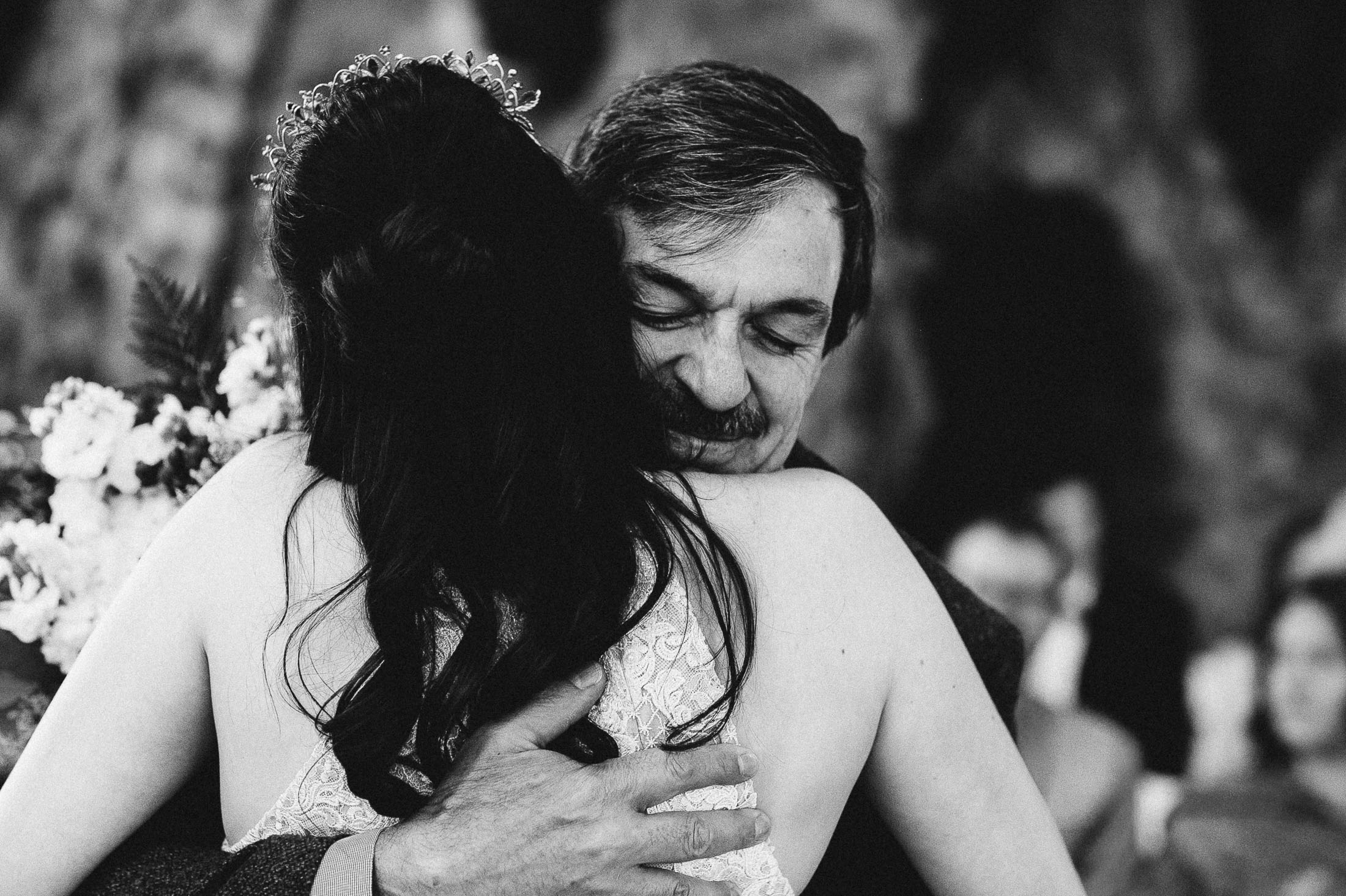 Black and white photo of father and bride hugging during ceremony at Bishop Castle.