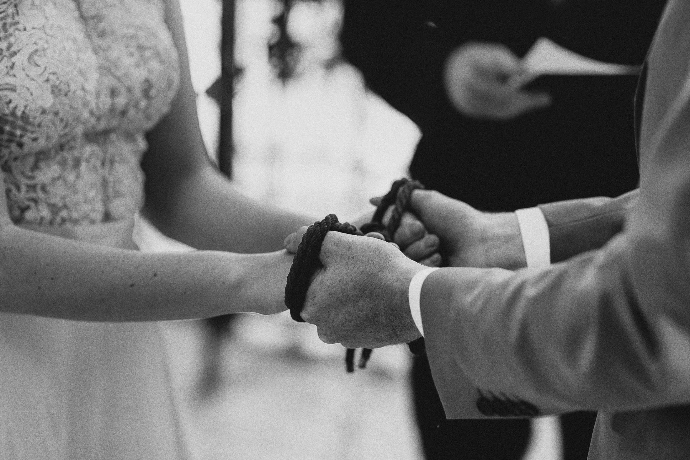 Black and white photo of bride and groom holding hands with ropes wrapped around their hands.