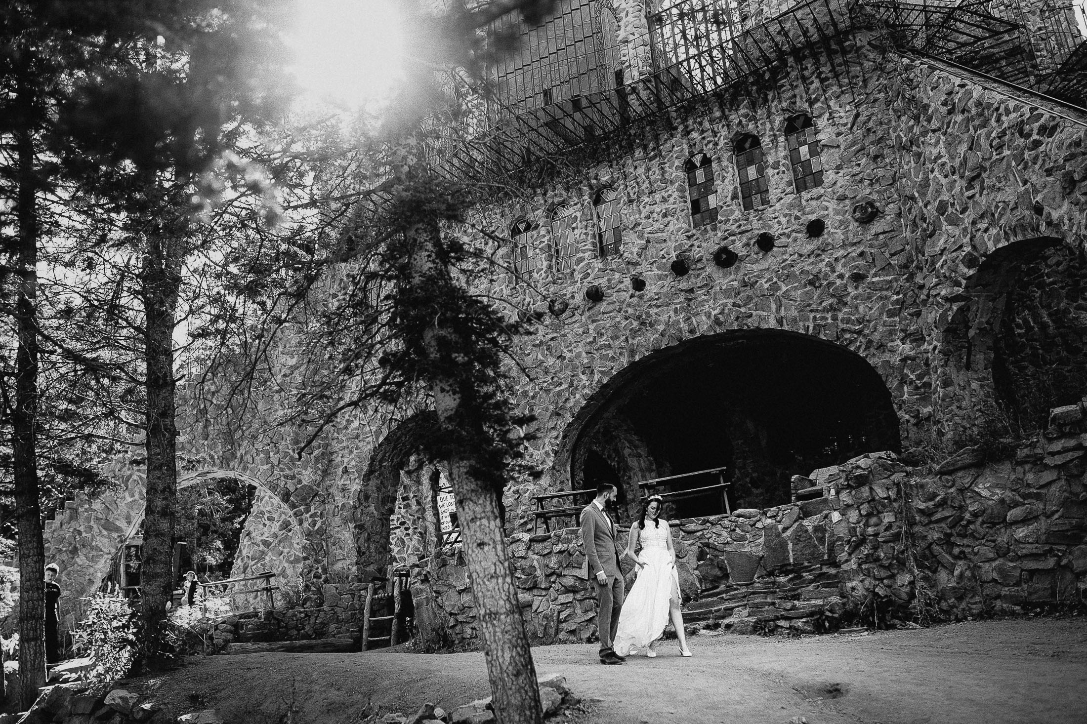Black and white photo of bride and groom walking in front of Bishop Castle on their wedding day.