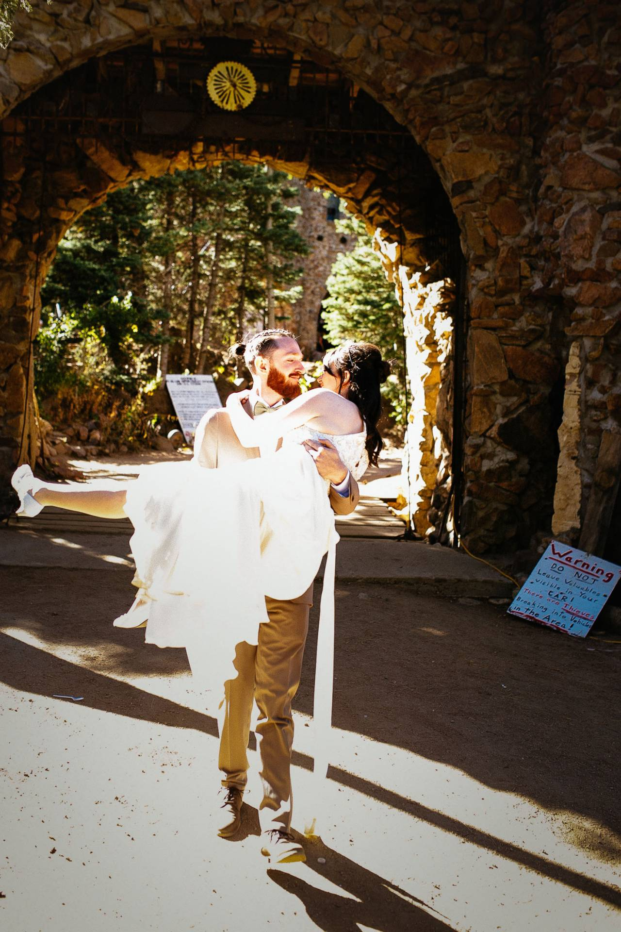 Groom carries bride from the entrance to the Bishop Castle on their wedding day.