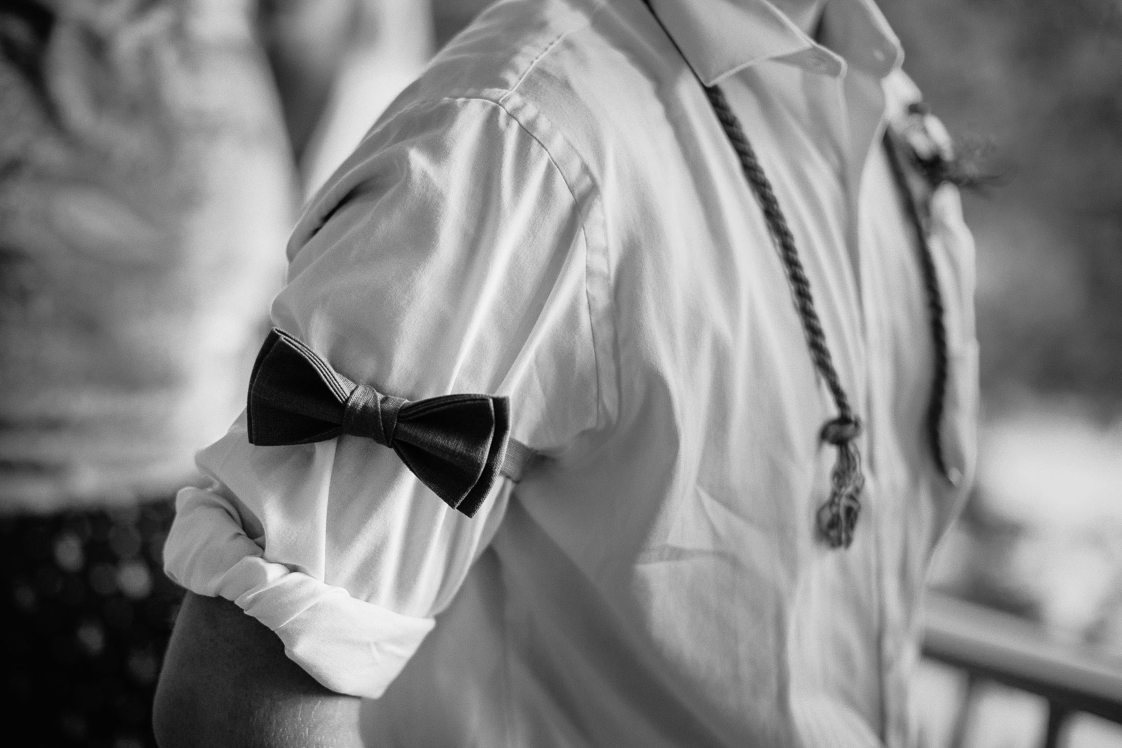 Black and white photo of wedding guest wearing bow tie on his arm.