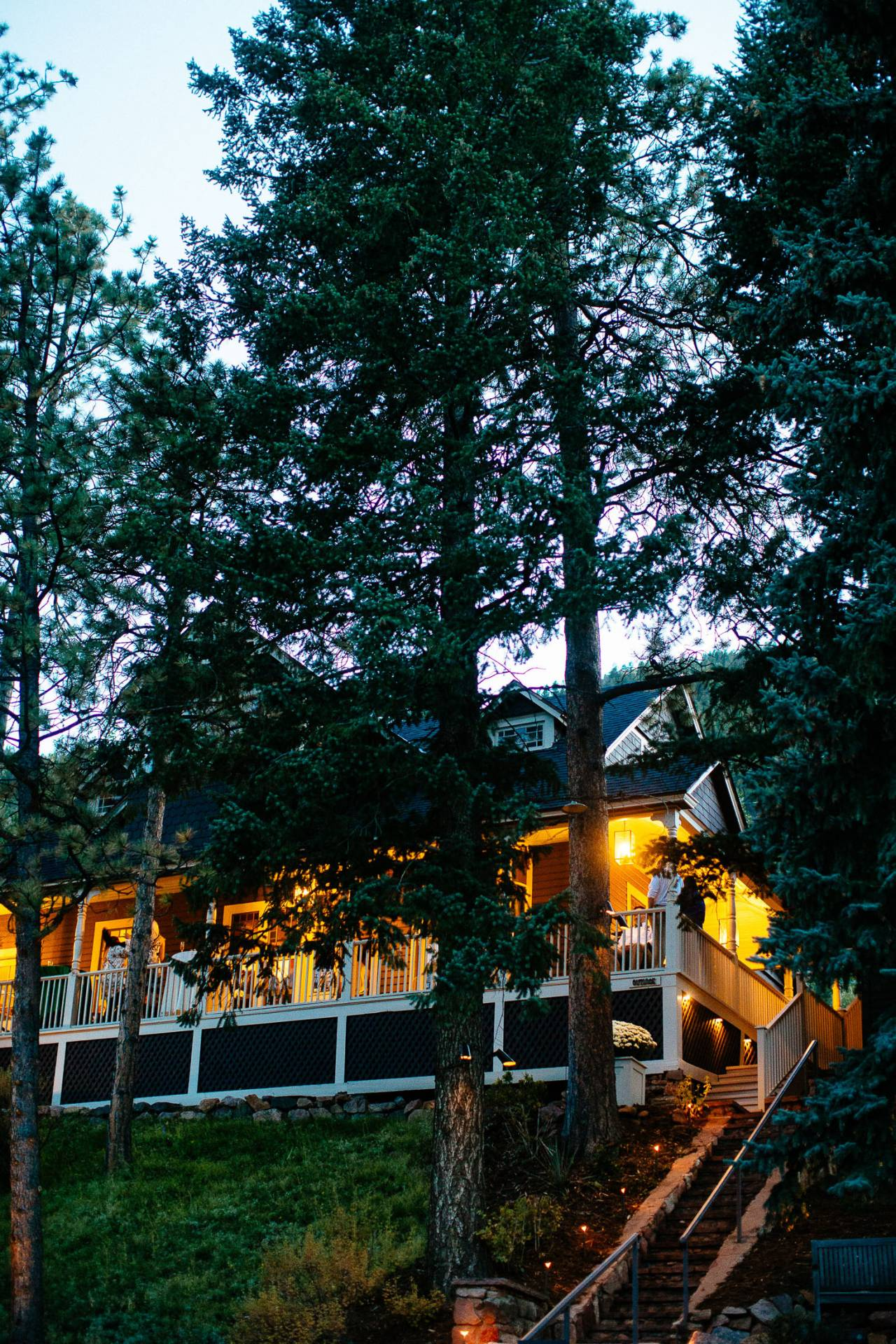 Outdoor photo of the Outlook Lodge surounded pine trees during wedding reception in Green Mountain Falls.