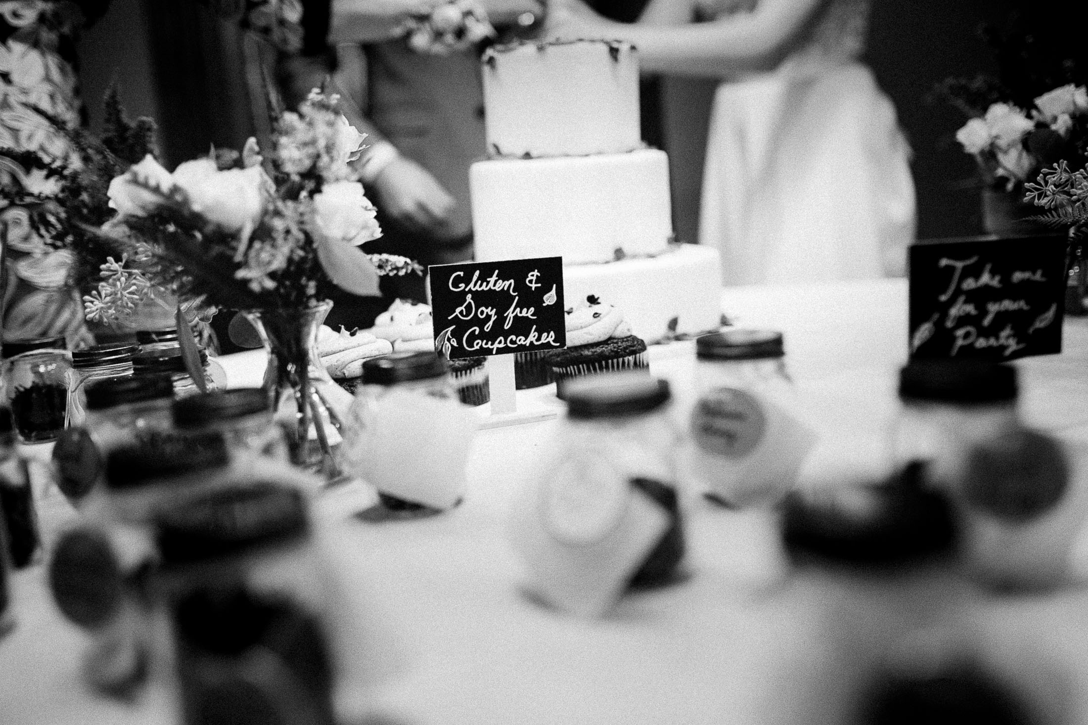 Black and white photo of wedding cake with chalk sign.