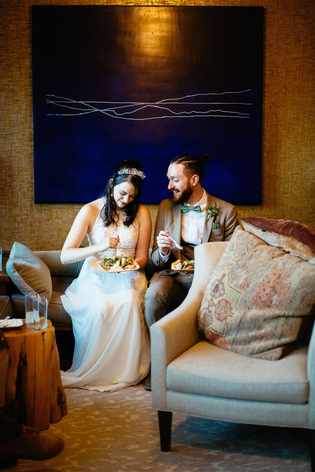 Wedding couple sits on couch with food during reception at the Outlook Lodge.