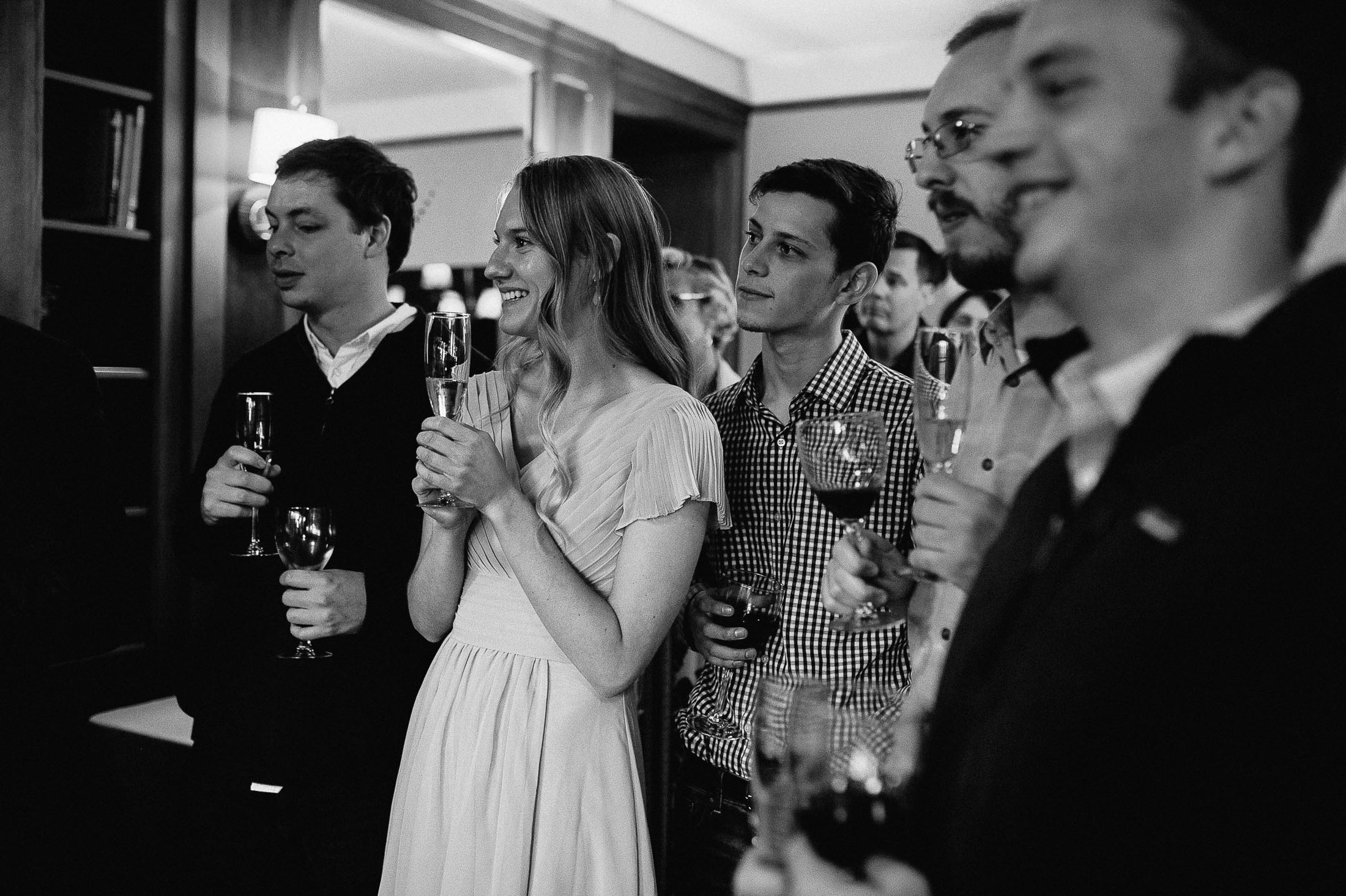 Black and white photo of wedding guests holding champagne flutes during wedding reception at the Outlook Lodge.