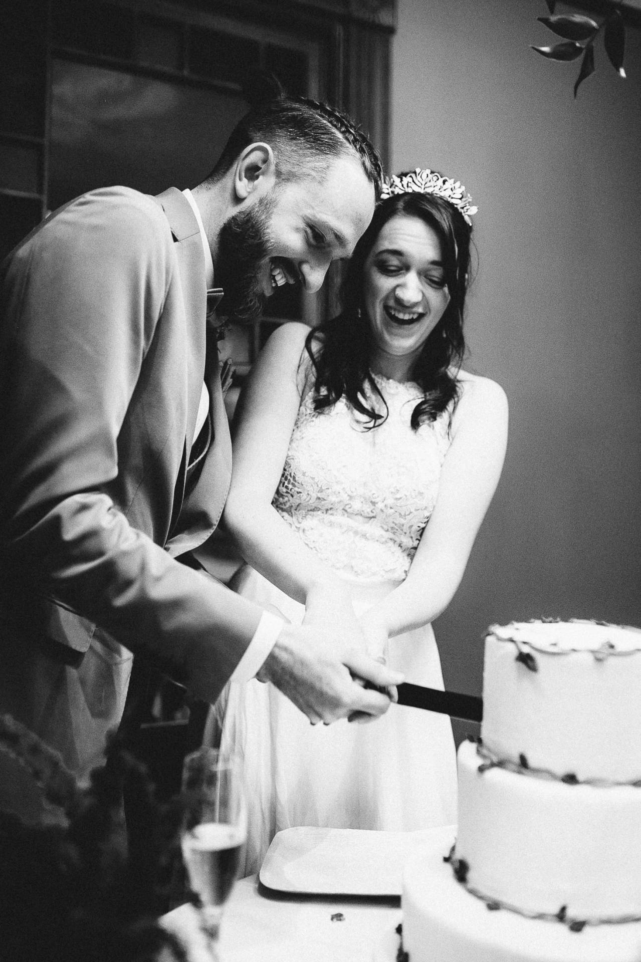 Black and white photo of couple cutting wedding cake at the Outlook Lodge.