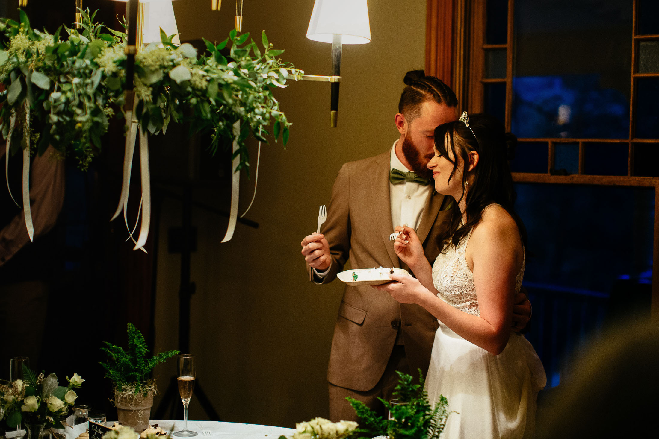 Couple kiss and hold plate with wedding cake during wedding reception at the Outlook Lodge.
