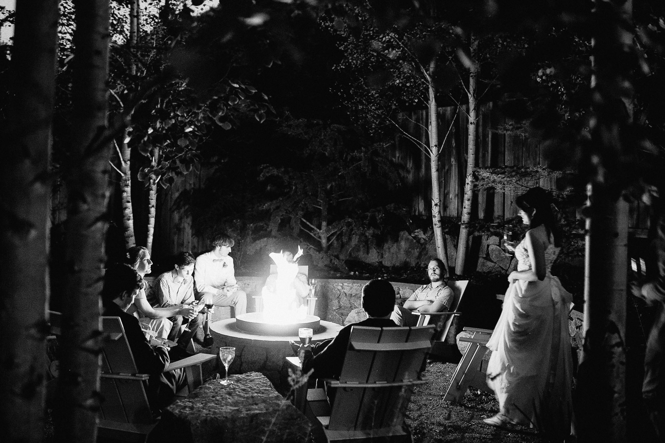 Black and white photo of firepit with wedding guests sitting beside it at the Outlook Lodge in Green Mountain Falls..