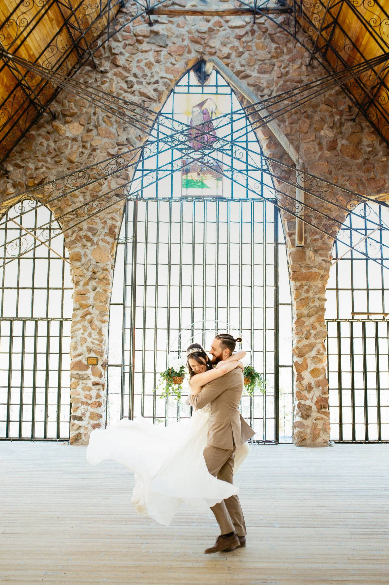 Groom holds bride inside Bishop Castle and twirles her around.
