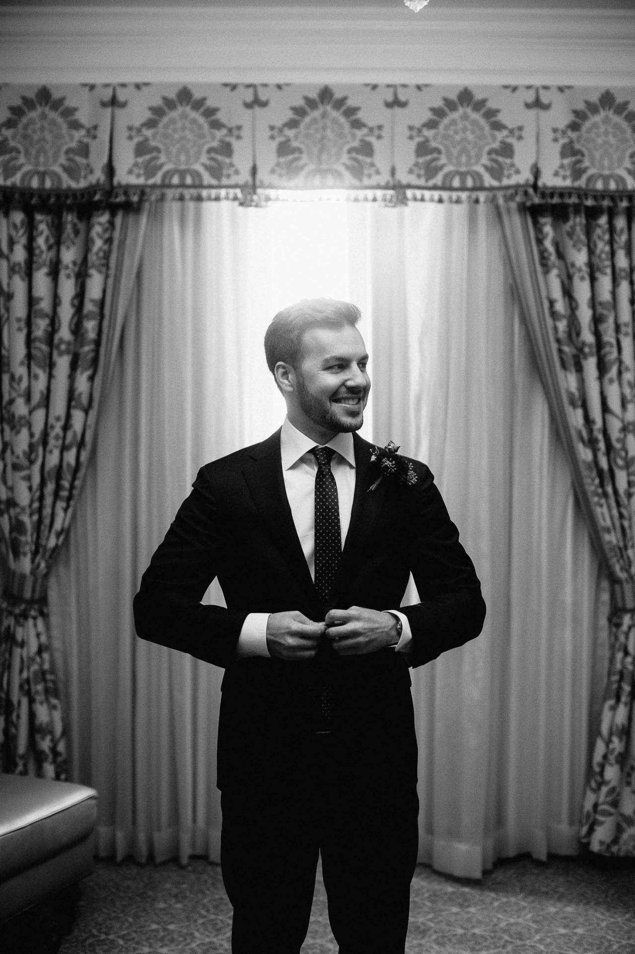 Black and white picture of groom adjusting his coat.