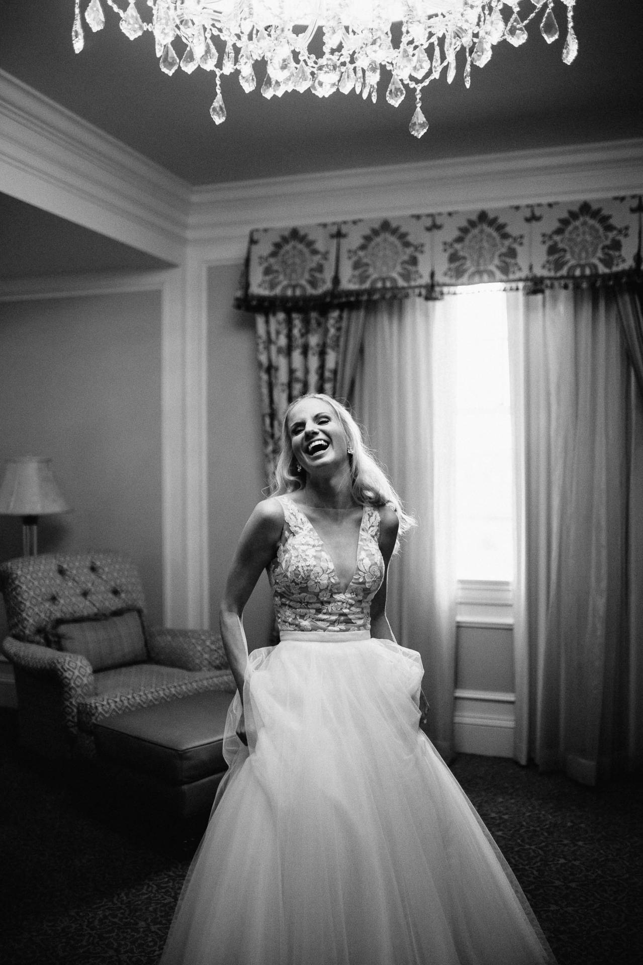 Black and white picture of bride laughing in bridal suite.