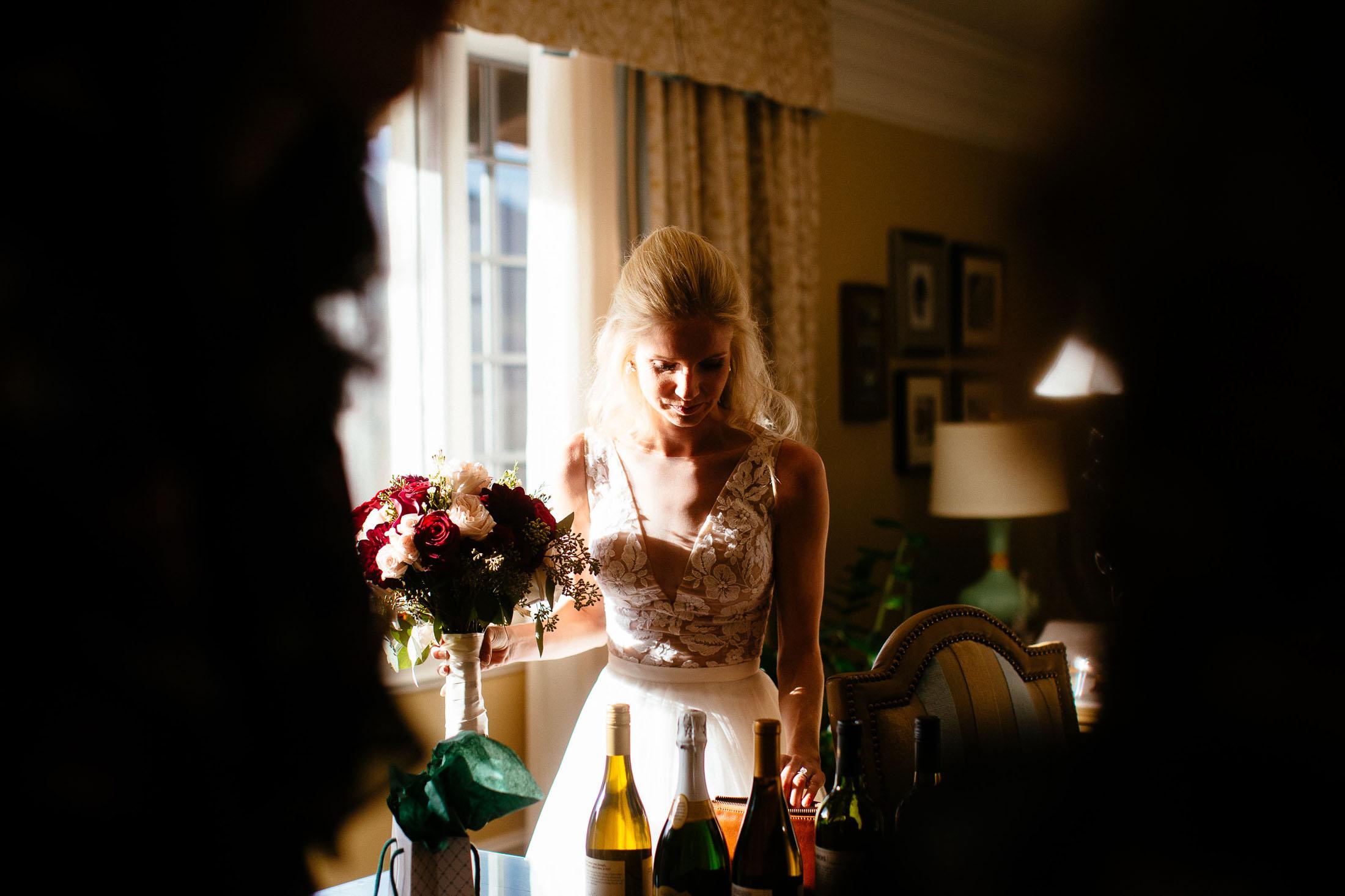 Bride standing window light with wine bottles.