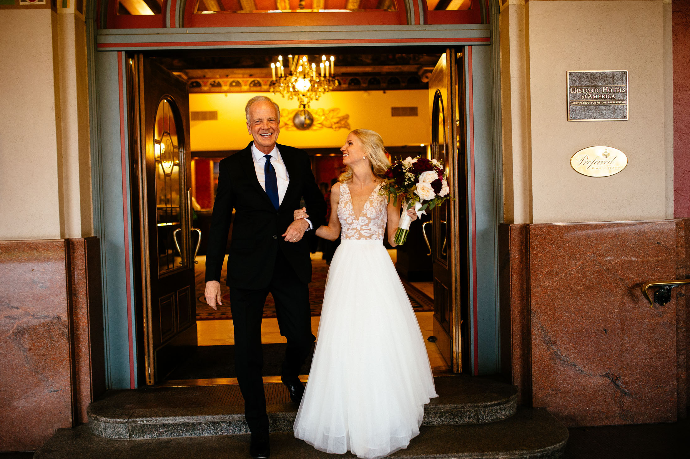Bride holding hands and walking out the main doors of The Broadmoor Hotel.