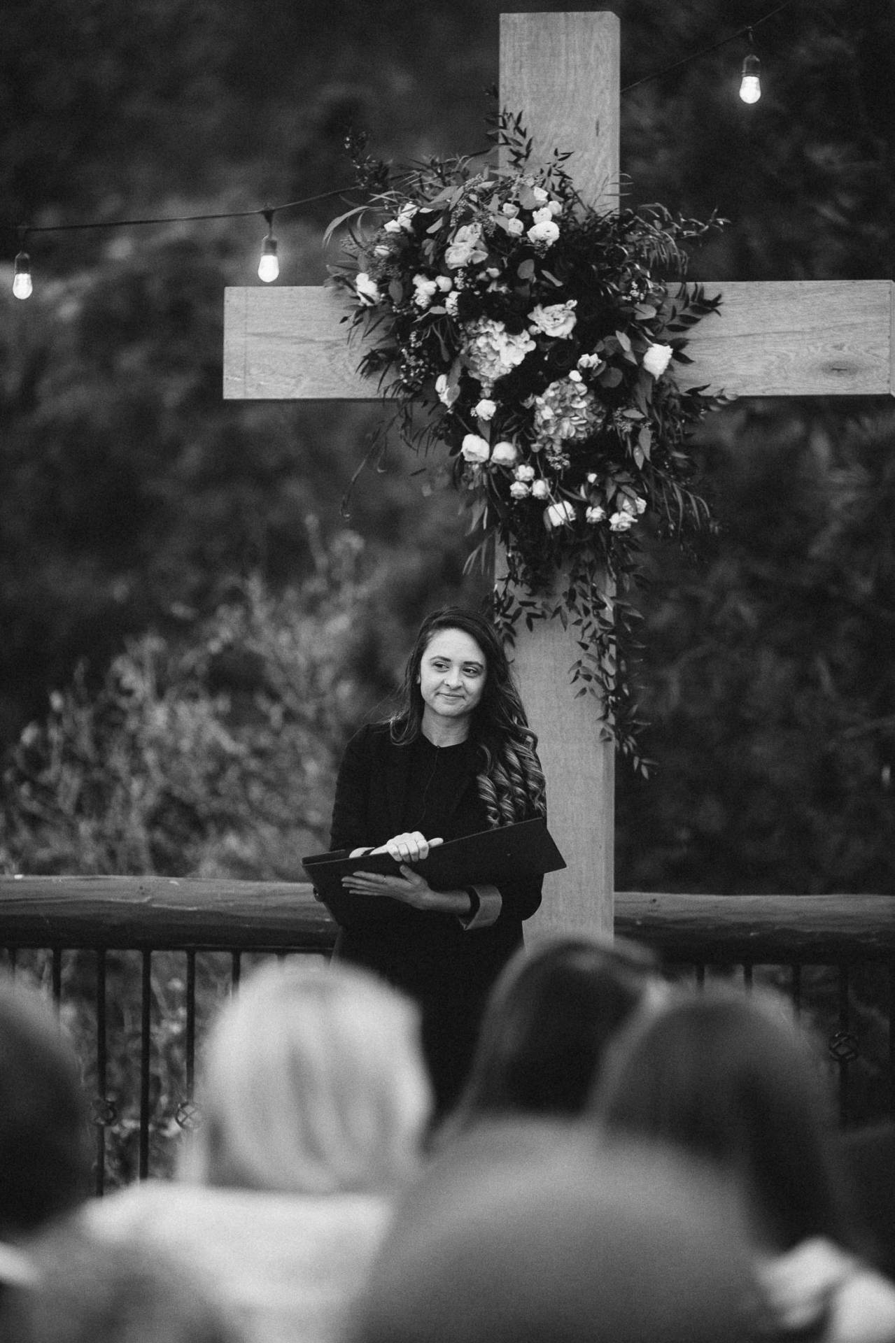 Black and white photo of minister standing at altar during wedding ceremony.