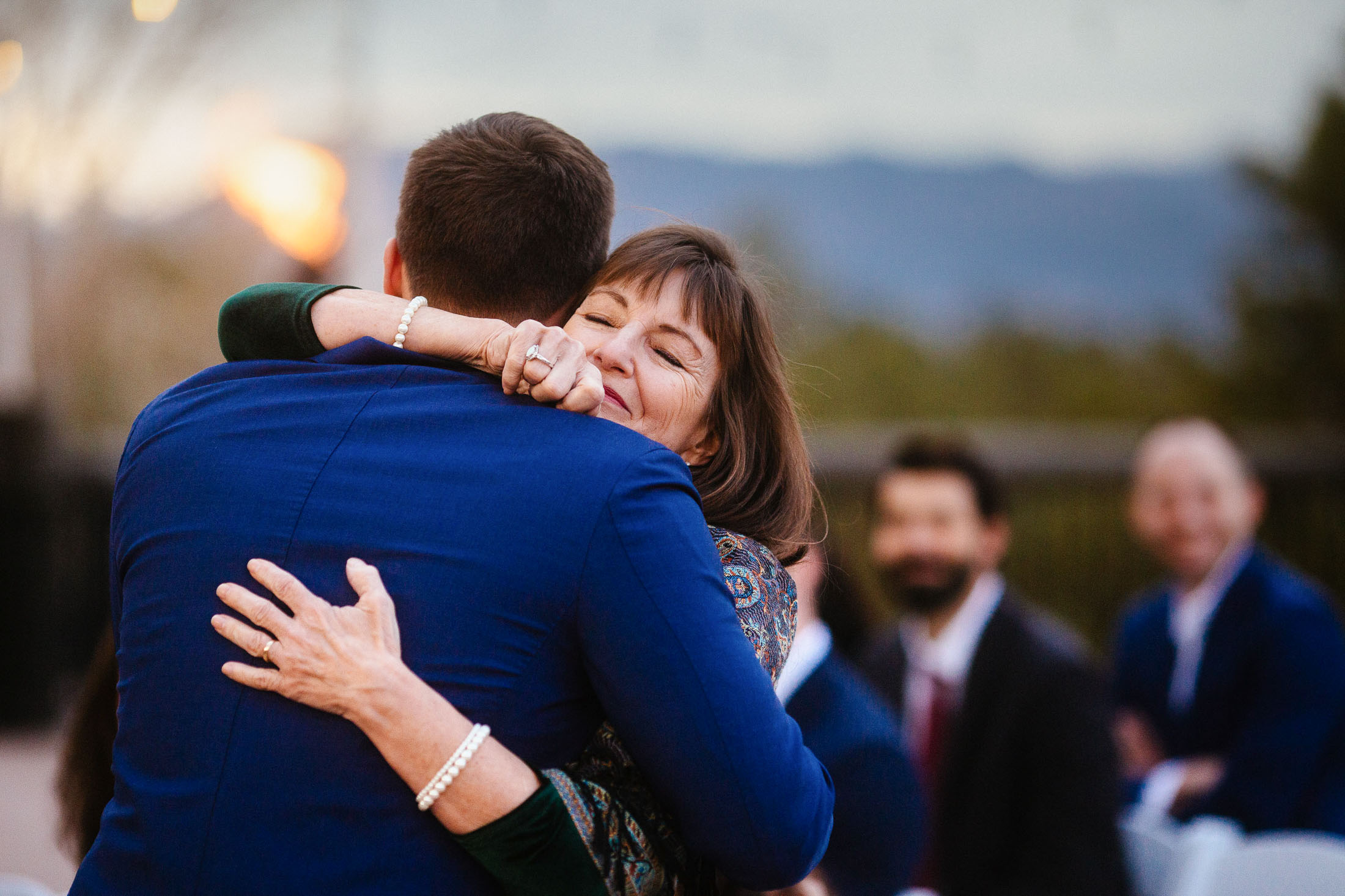 Mother of the groom hugs her son during wedding ceremony.