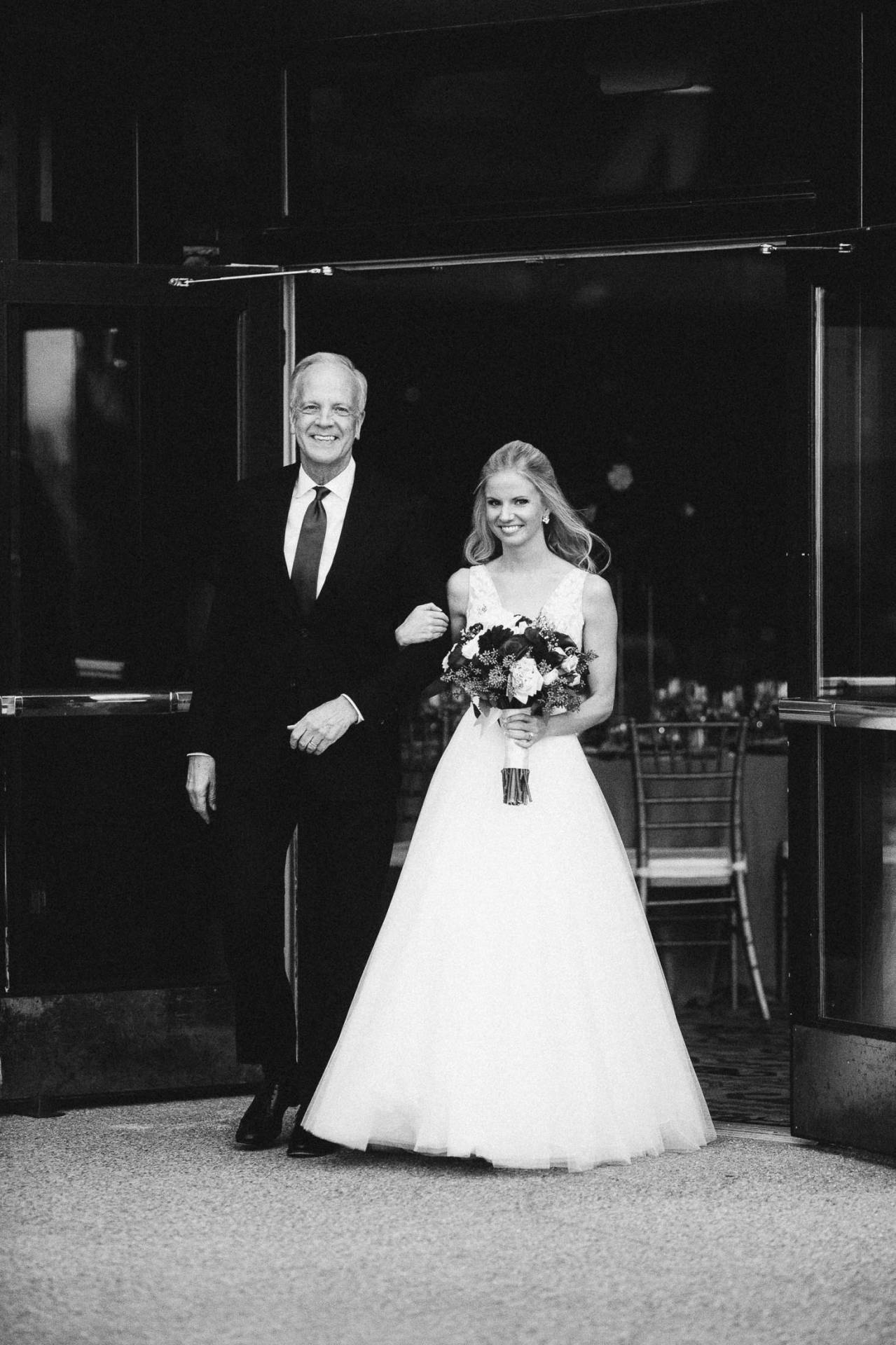Black and white photo of father and daughter walking arm-in-arm down the aisle.