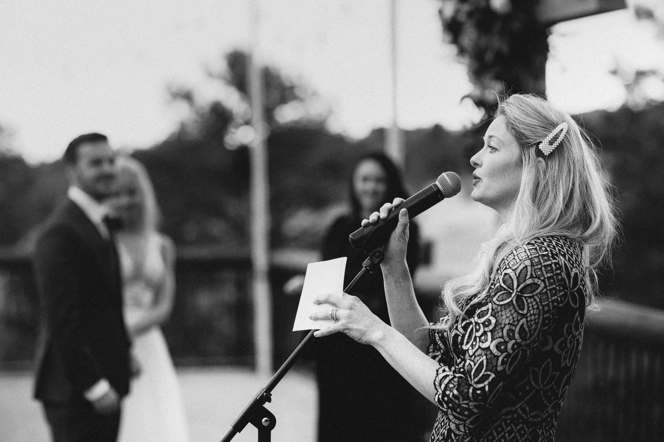 Black and white picture woman singing during wedding ceremony.