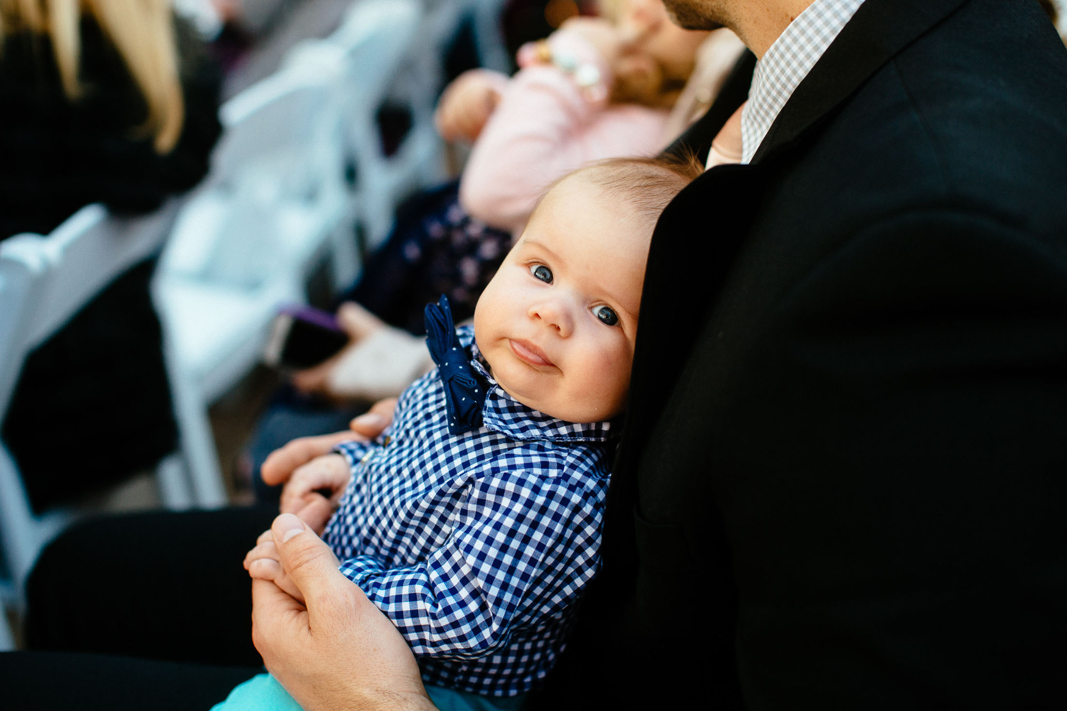 Portrait of baby sitting in a lapr during wedding ceremony.
