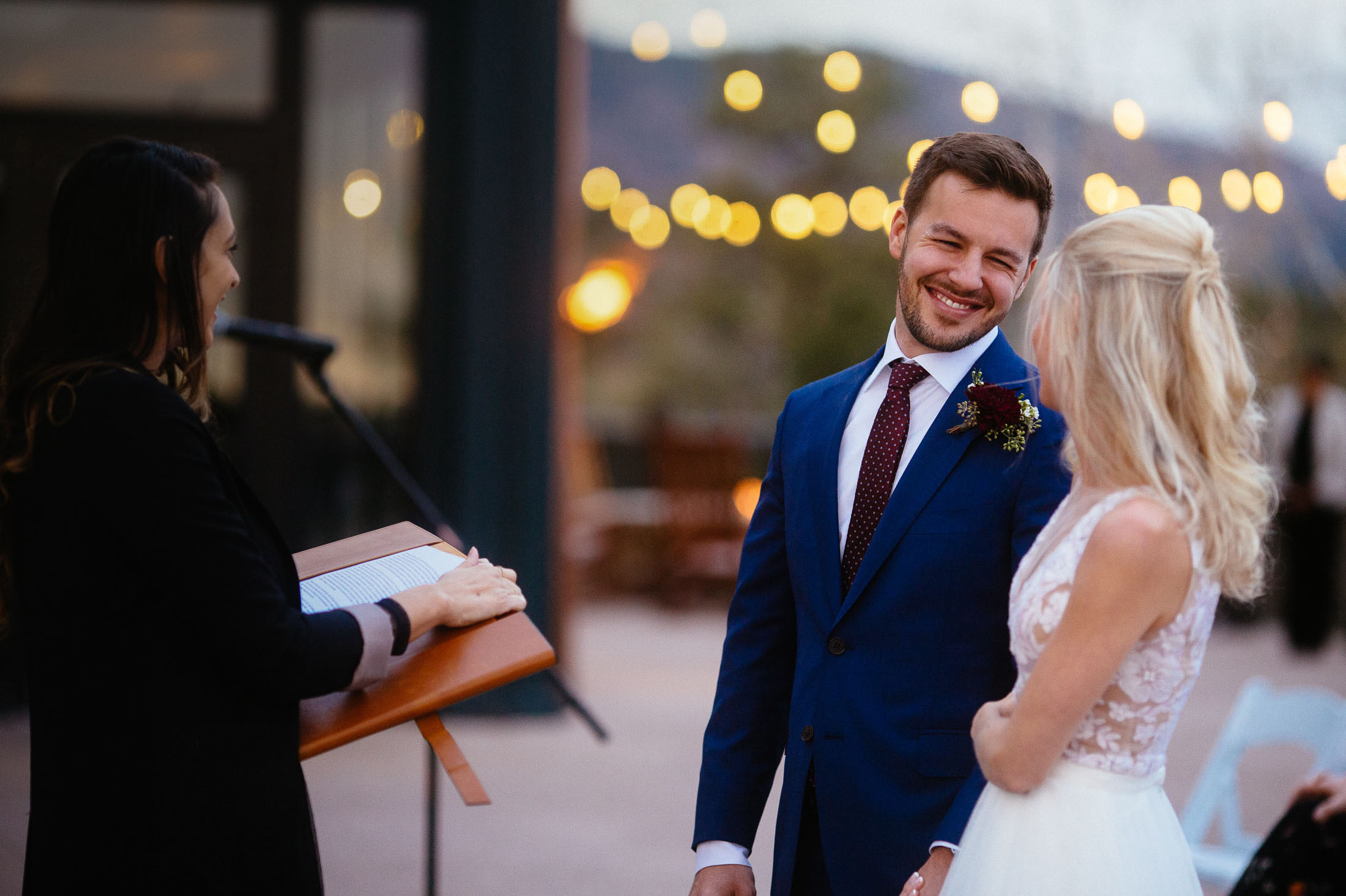 Grooms smile at bride during wedding ceremony.