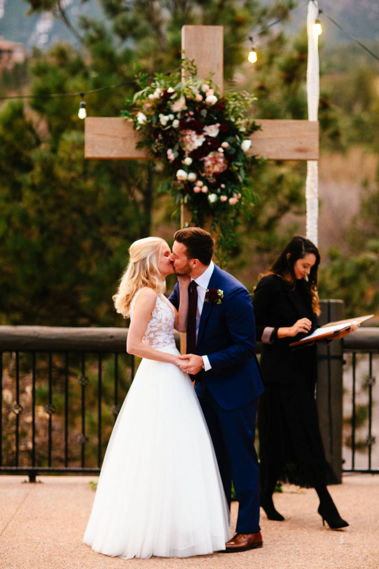 Bride and groom kiss at the altar with cross in the background during wedding ceremony at Cheyenne Lodge.