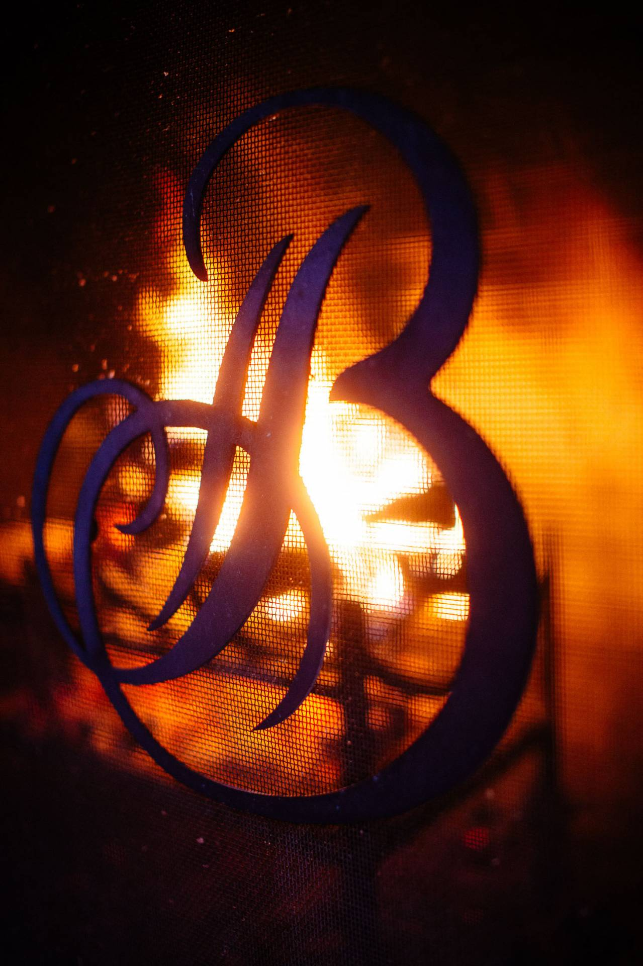 Fireplace with flames and the letter B logo from The Broadmoor at the Cheyenne Lodge.