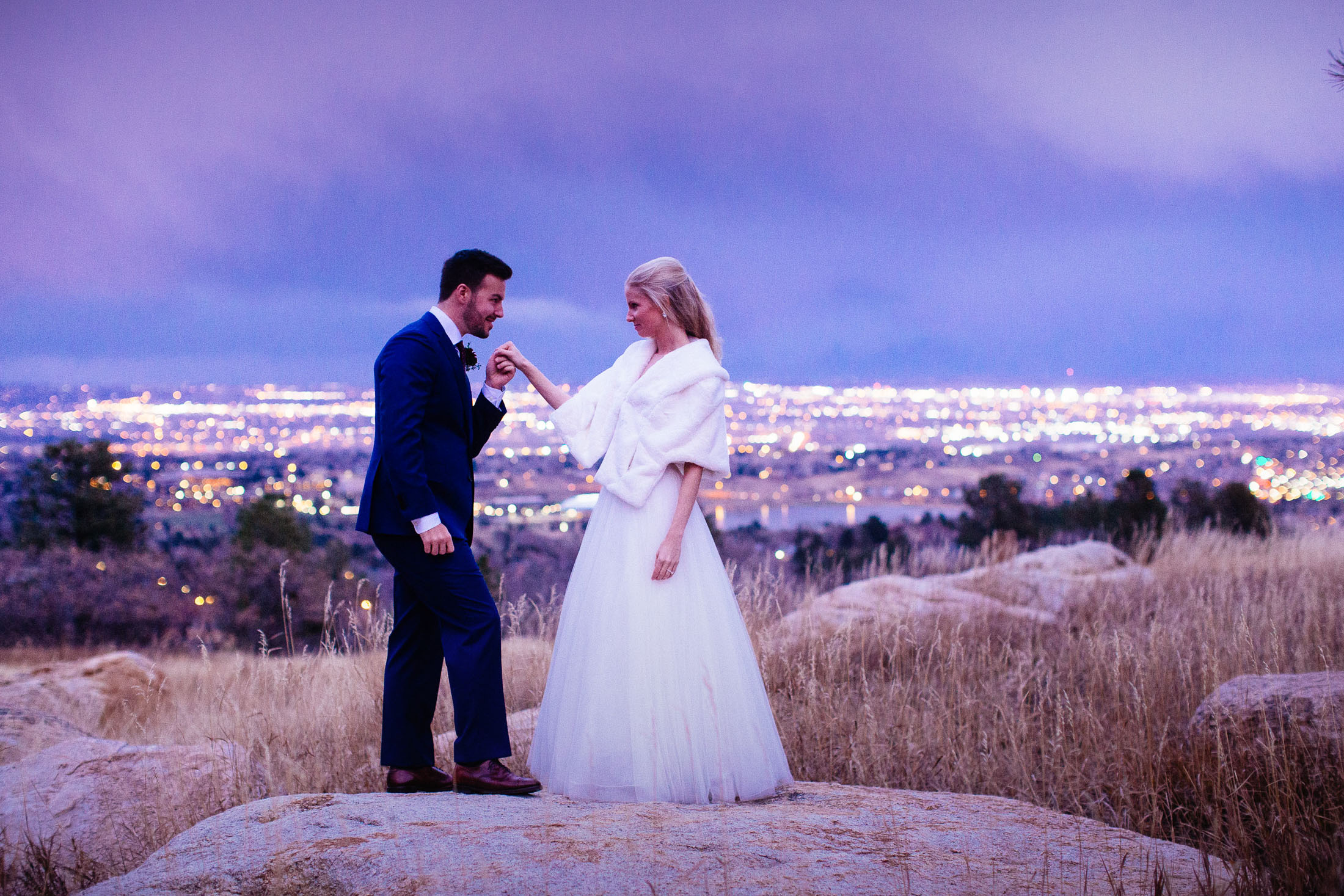 Groom kisses bride's hand as they stand on a rock overlooking the city of Colorado Springs at night.