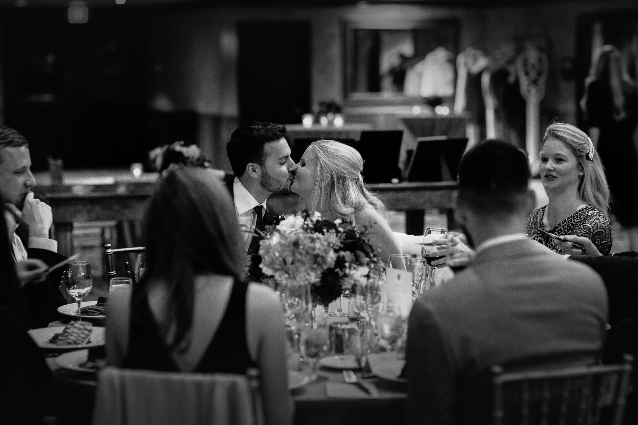 Black and white photo of bride and groom kissing during dinner reception in the Cheyene Lodge.