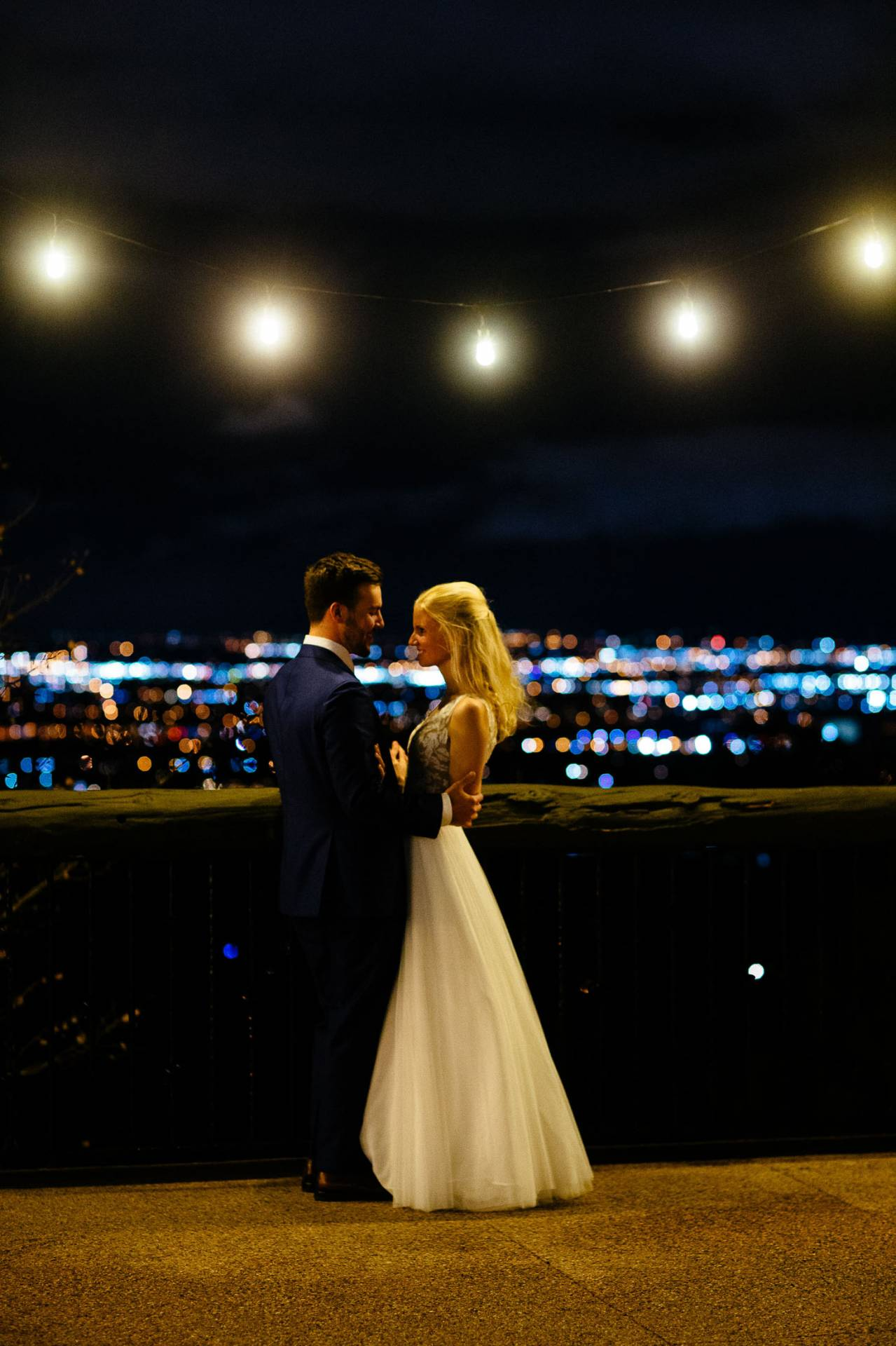 Bride and groom embrace on the deck outslide the Cheyenne Lodge with city lights in the background.