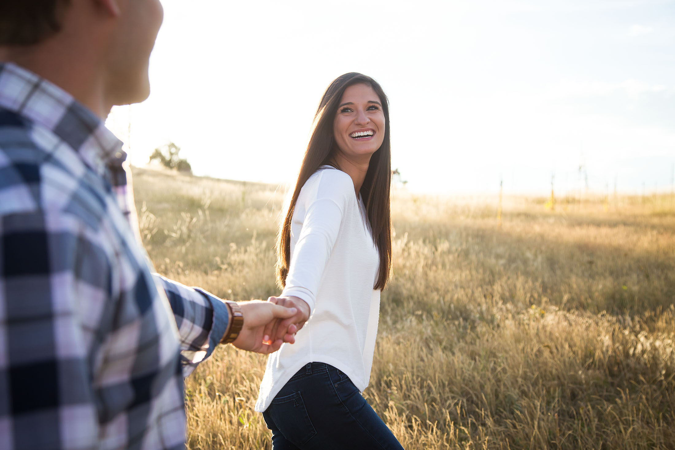 Woman walks through a sunlit field and looks back at her partner.