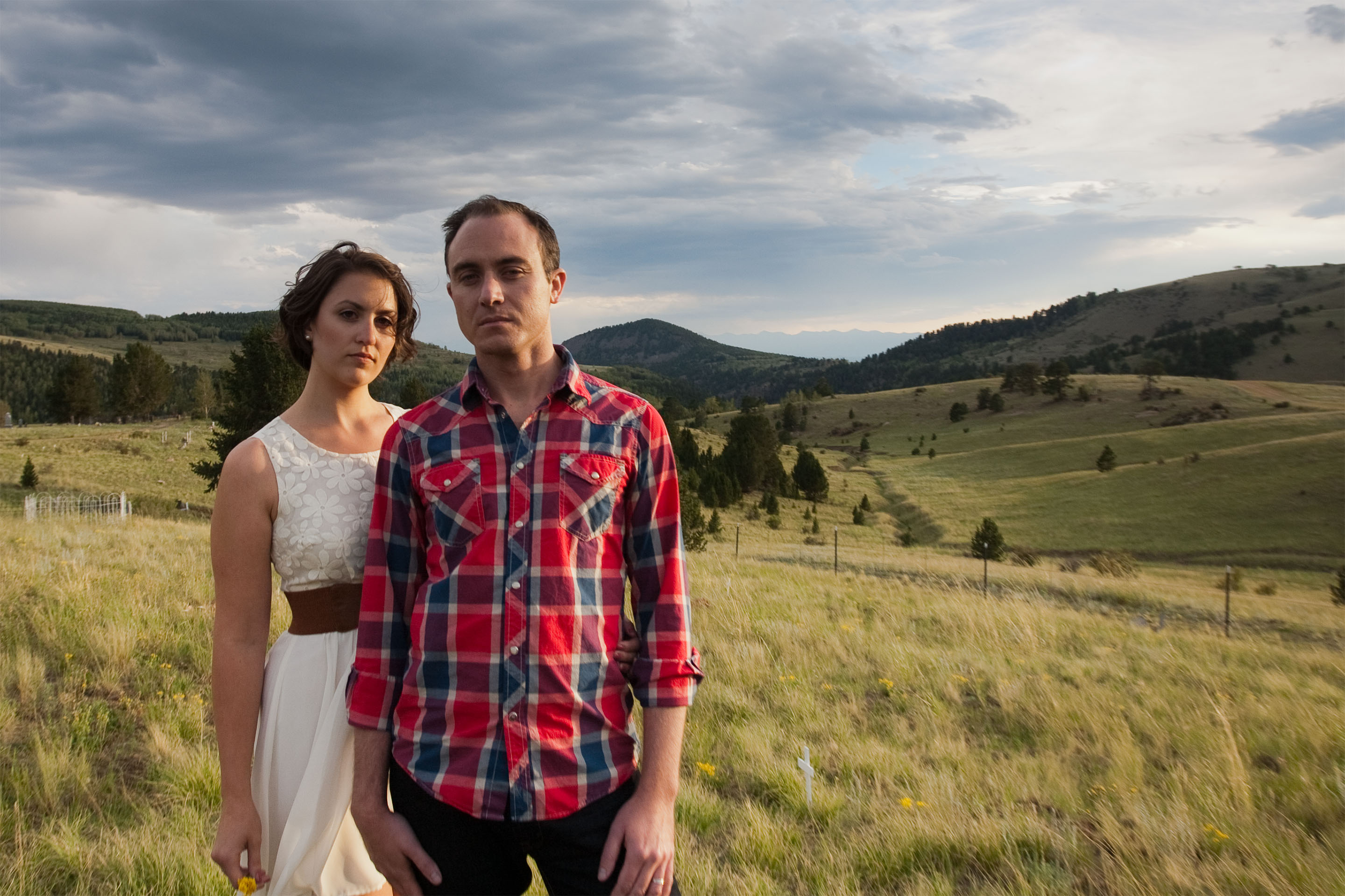 Couple stands together on a hillside at sunset in Victor, Colorado.