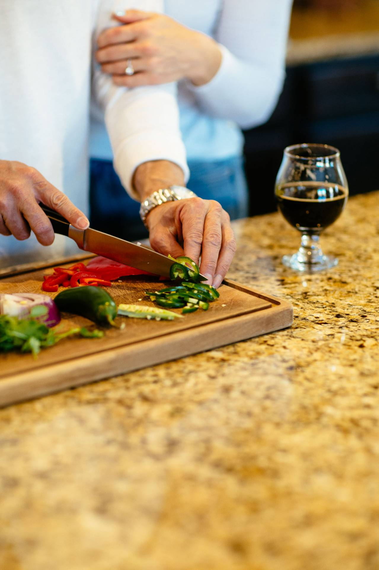 Man cuts vegatables with knife on cutting board.
