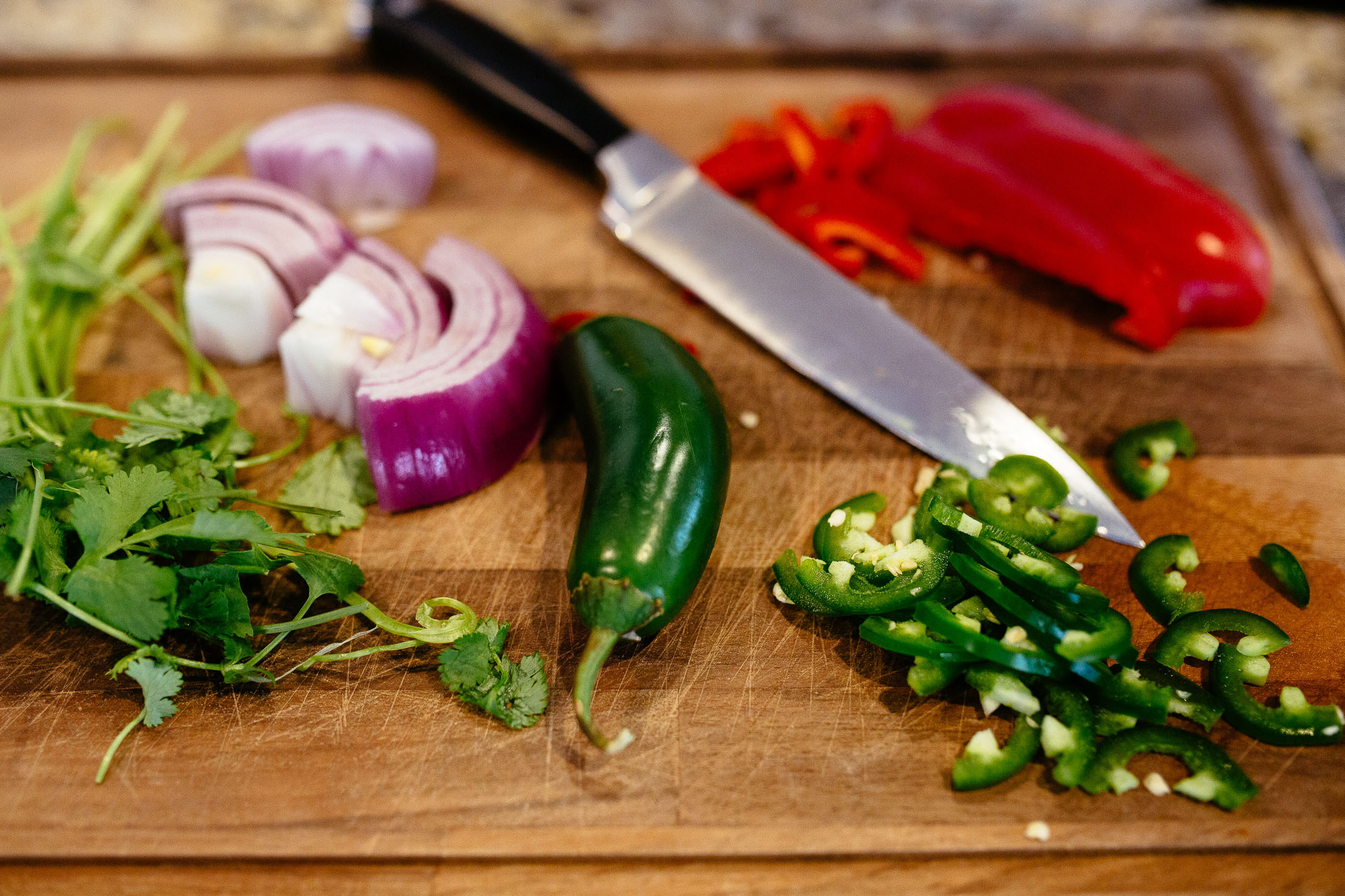 Vegetables and knife on a cutting board.